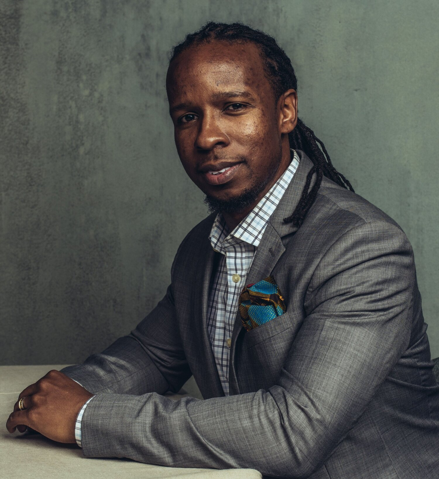 Ibram X. Kendi has his hands clasped and arms resting on a table.