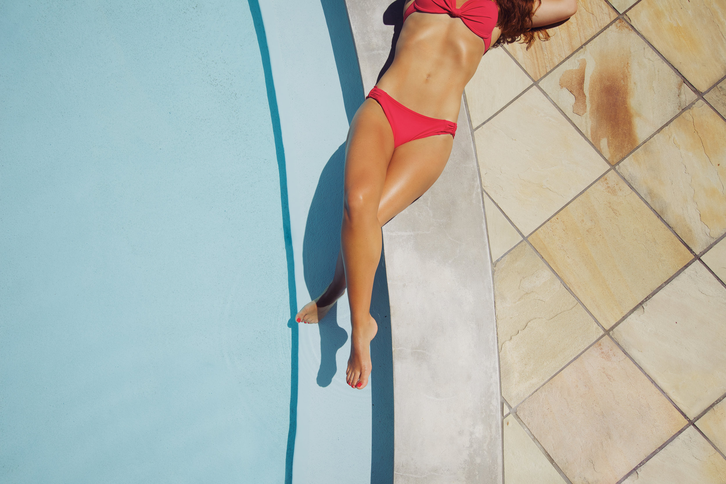 high-angle-view-of-an-attractive-woman-lying-at-the-edge-of-a-pool-in-a-bikini-with-her-legs-crossed-female-model-sunbathing-at-poolside_HpbYgSIVFx.jpg
