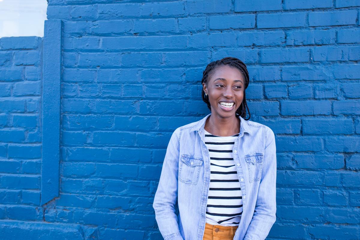 Girl in denim jacket with blue brick background