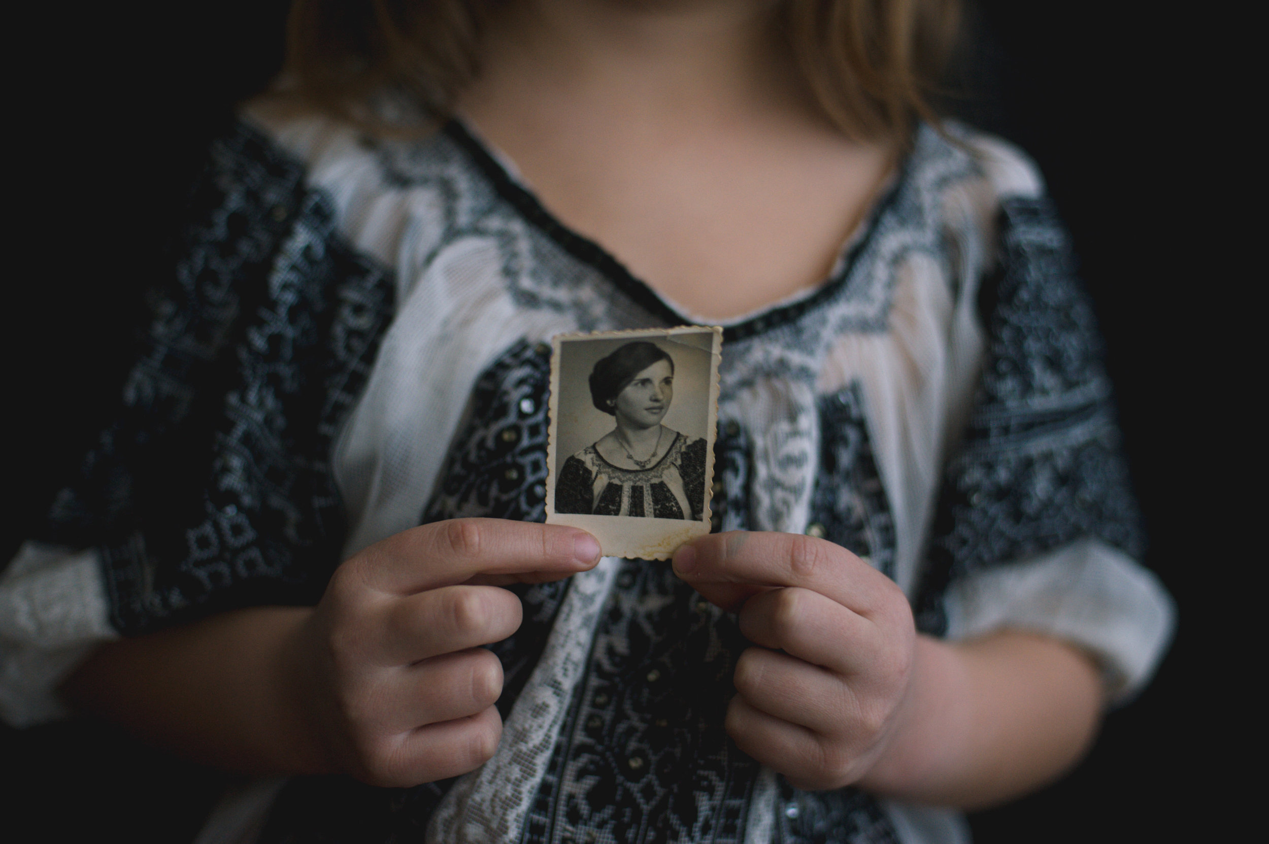 Adina's daughter, Ilinca (5), wears the same embroidered shirt as her grandmother (Adina's mother) in the photo she holds.