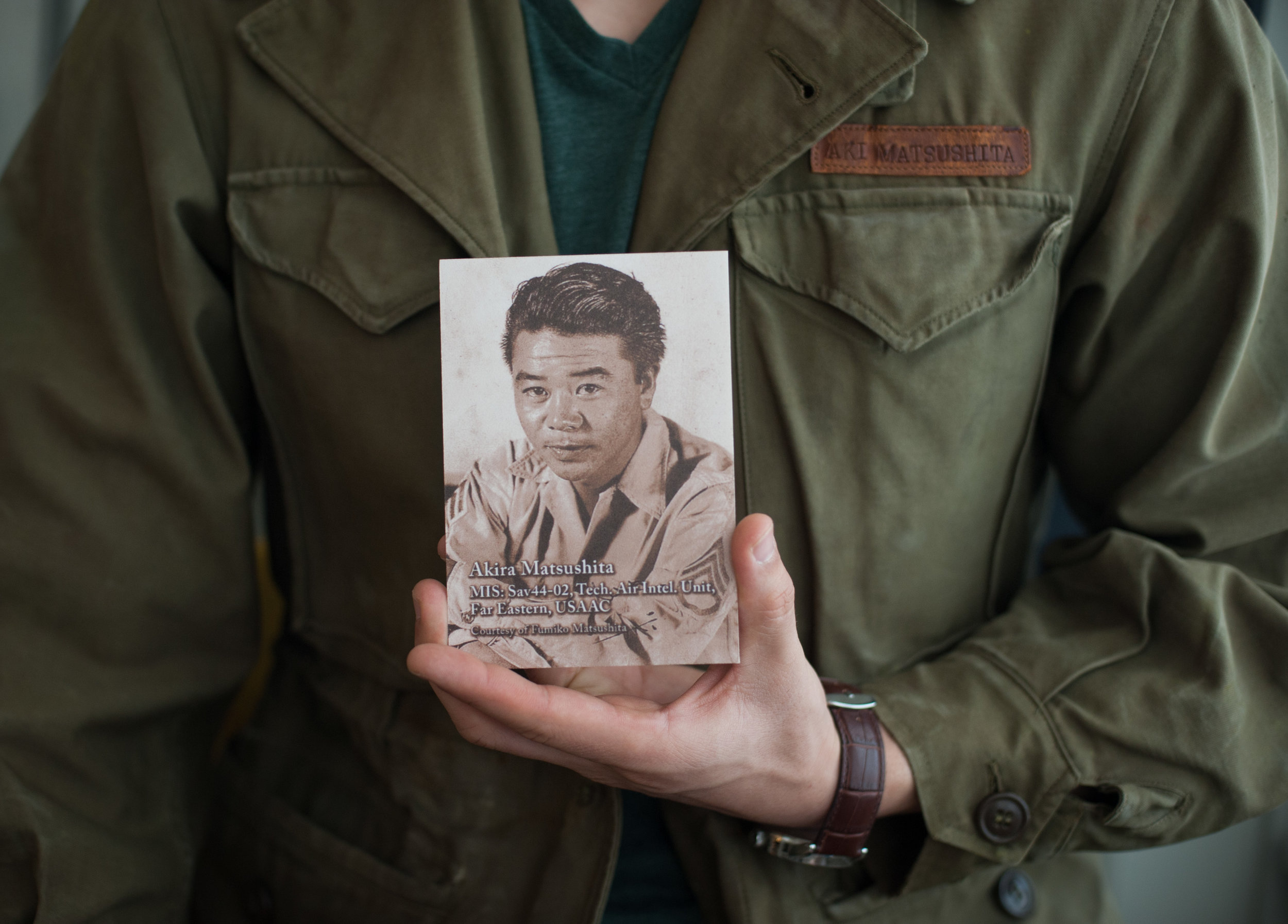 Josh, wearing his grandfather's US Army jacket and holding his grandfather's US Army photo.