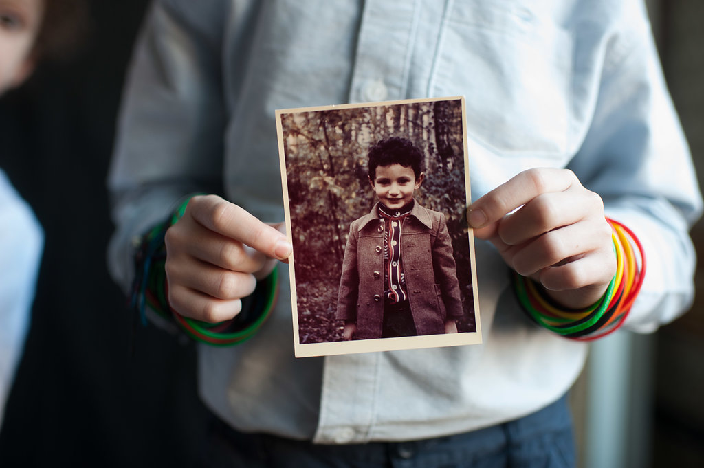 Phil's son holds a picture of Phil as a child in Moscow.