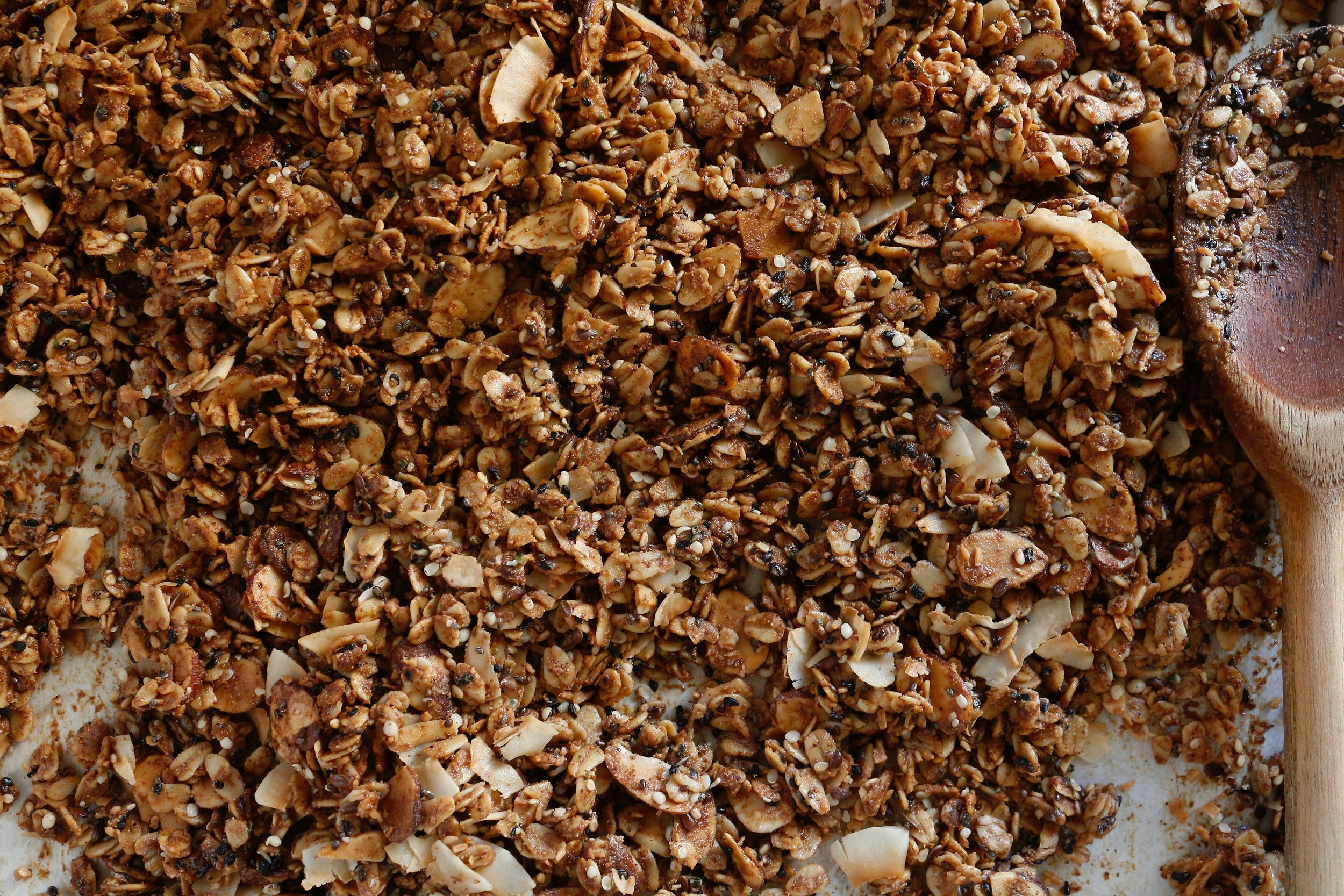"Sometimes granola gets a bad rap- everyone loves it, but then there's the thing about it having ""soooo many calories."" Sure, if calorie counting and pre-packaged, mass-produced granola is what you're used to then you're probably right. But the beauty of cooking from scratch is not just that it's soul-feeding, it's that you have control over what to include in/ exclude from your food.  This recipe bridges the gap between sweet and savory with flaky sea salt and natural sweeteners like coconut sugar and maple syrup. Floral notes in cardamom complement seasonal fruits at breakfast and sharp vinaigrettes at lunch. Be sure to toast the coconut separately, as it cooks much faster than the rest of the mixture and would definitely burn after 30 minutes. Feel free to swap out some of the seeds and nuts based on what you have on hand, but try to keep the total weight of the uncooked oat mixture to about 495g to keep a good ratio of wet to dry ingredients.     Recipe     makes about 5 cups   335g Bob's Red Mill extra thick rolled oats  80g sliced almonds, raw  20g white sesame seeds, raw  20g black sesame seeds, raw  20g chia seeds  20g flax seeds  20g unsweetened large coconut flakes, raw  20g unsweetened fine coconut flakes, raw  20g hemp hearts, raw  180g roasted unsalted smooth almond butter  100g virgin coconut oil  15g maple syrup  25g coconut sugar  1/2 teaspoon freshly ground cardamom  5g flaky sea salt        Method    Preheat oven to 350F degrees. Place coconut flakes on a baking sheet lined with parchment paper and toast until perfectly golden brown and fragrant, about 6 minutes. Transfer toasted coconut to a small bowl and combine with hemp hearts and set aside.   In a large bowl, combine oats, sliced almonds, sesame seeds, flax seeds, and chia seeds.   In a small pot, combine almond butter, coconut oil, maple syrup, coconut sugar, and ground cardamom and heat over medium until the coconut oil is completely melted and well combined. Crush the sea salt between your fingers and stir into the warm almond butter mixture. Pour the almond butter mixture over the oat mixture and stir until everything is evenly coated. Transfer to the baking sheet and spread into an even layer, then season again with a big pinch of flaky sea salt, leaving the crystals larger this time. Bake for 30 minutes, tossing halfway through. After 30 minutes, remove from the oven and stir in the toasted coconut and hemp hearts until evenly incorporated.   Allow granola to cool at room temperature before transferring to an airtight container.   Serve with yogurt and fruit, your milk of choice, or sprinkle into salads for crunch."