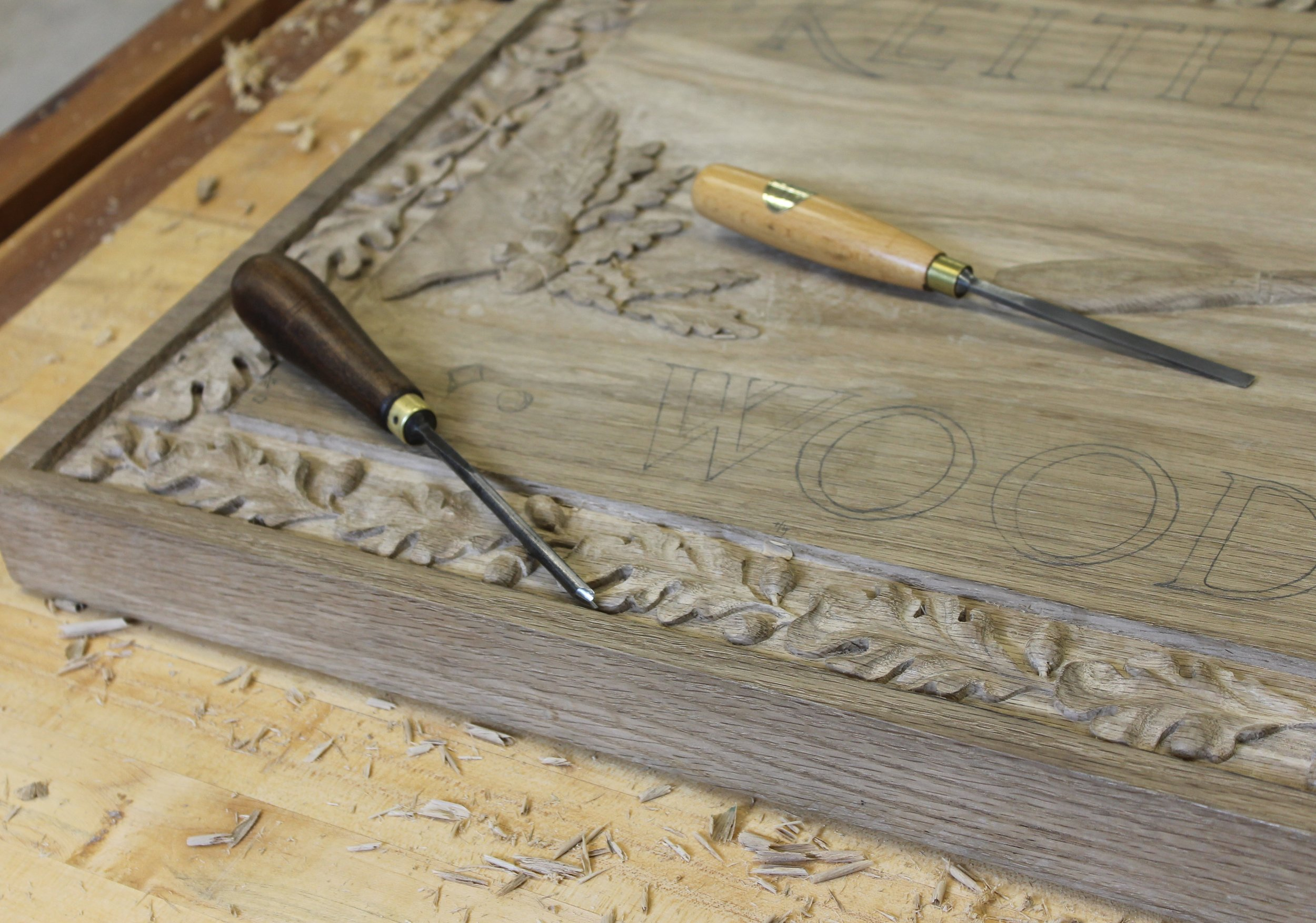 On the bench -  a  large panel in white oak  with incised lettering and oak leaf and acorn border