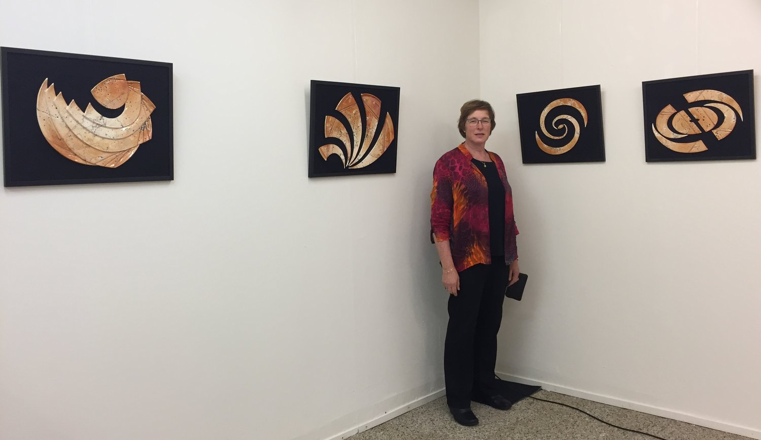 The artist, Swanica in front of her wall arts