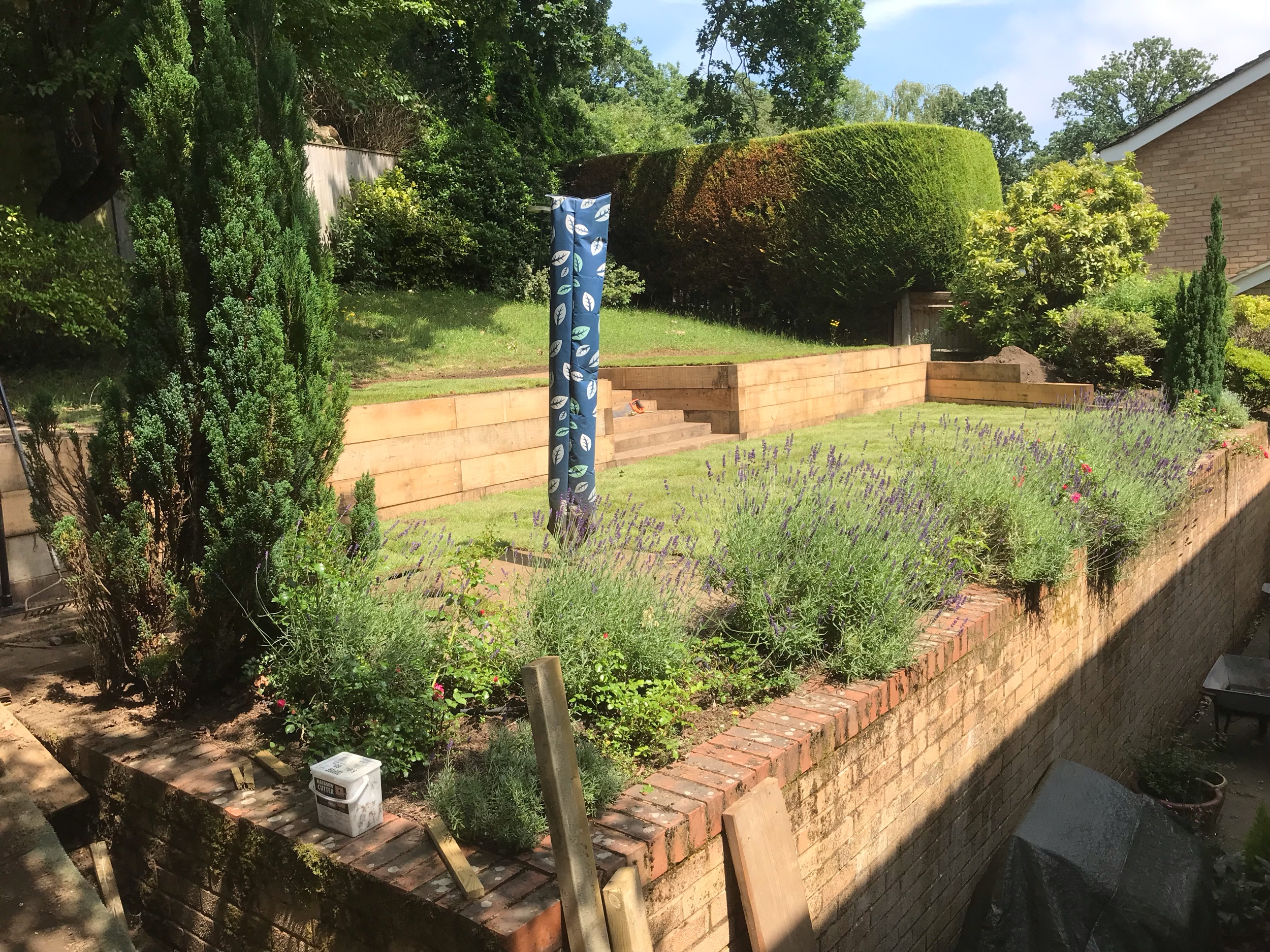 New sleeper retaining wall creating a usable level lawn from an unsightly bank.