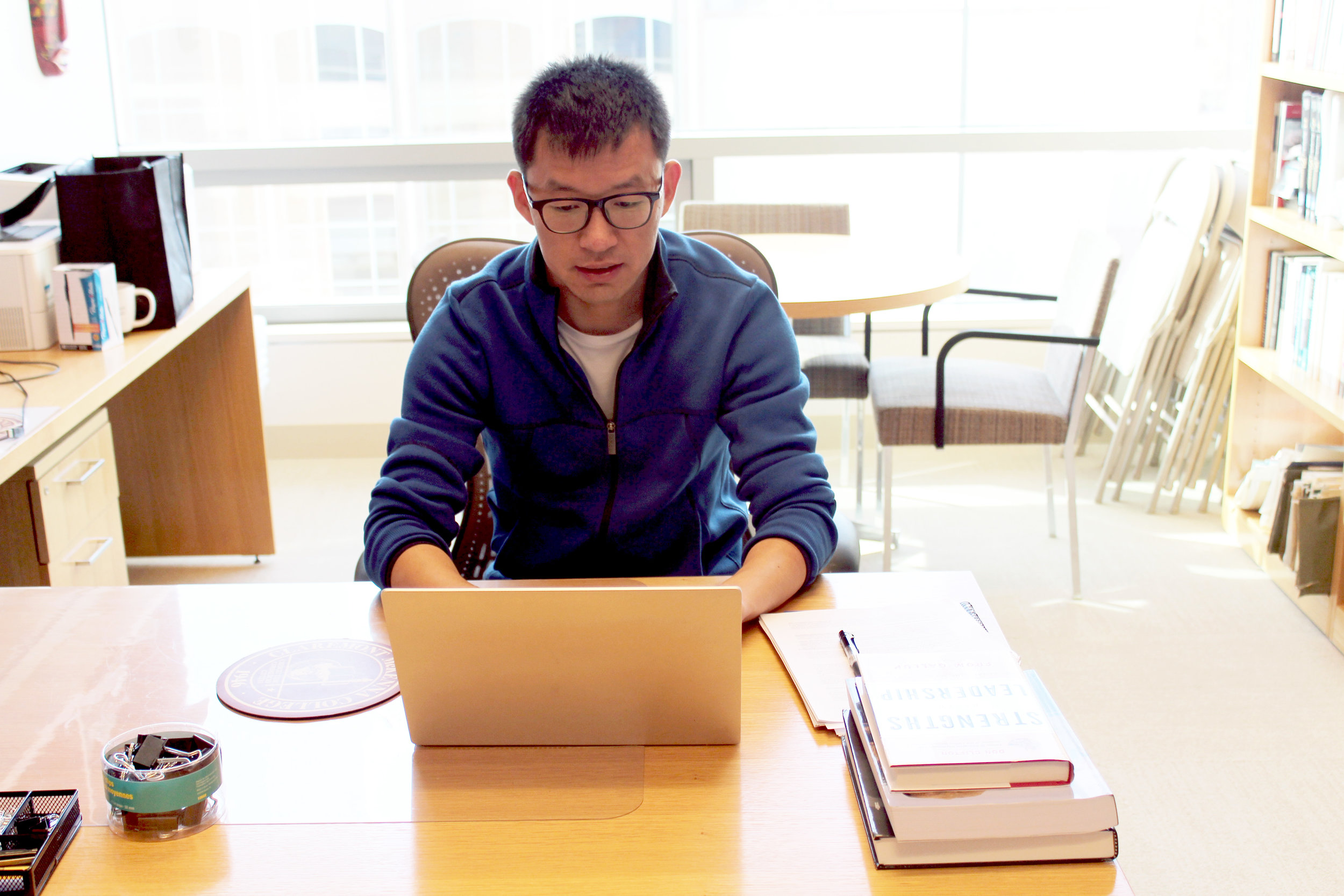 Marko Liu pictured working on leadership research data at Kravis Leadership Institute