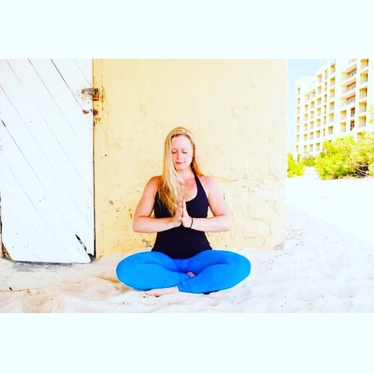 Mary in Sukhasana in Aruba against butter wall with blue pants.jpg