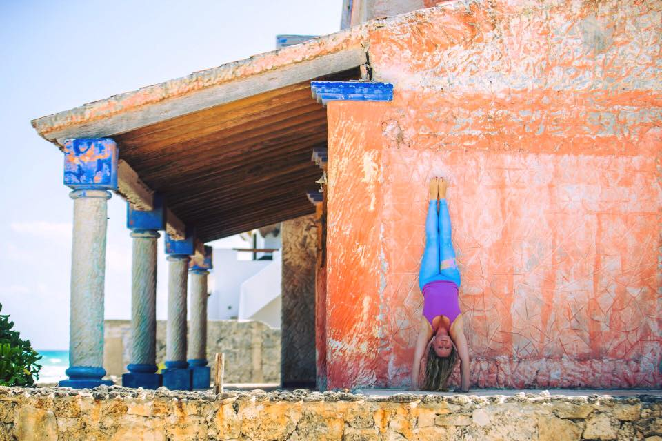 Hollow back handstand against orange wall in Tulum, in blue pants.jpg