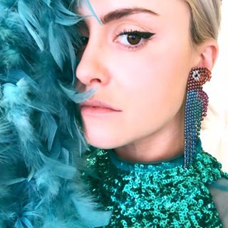 Greta Titleman looking fab in blue sequins, blue feathers, and blue beaded earrings.