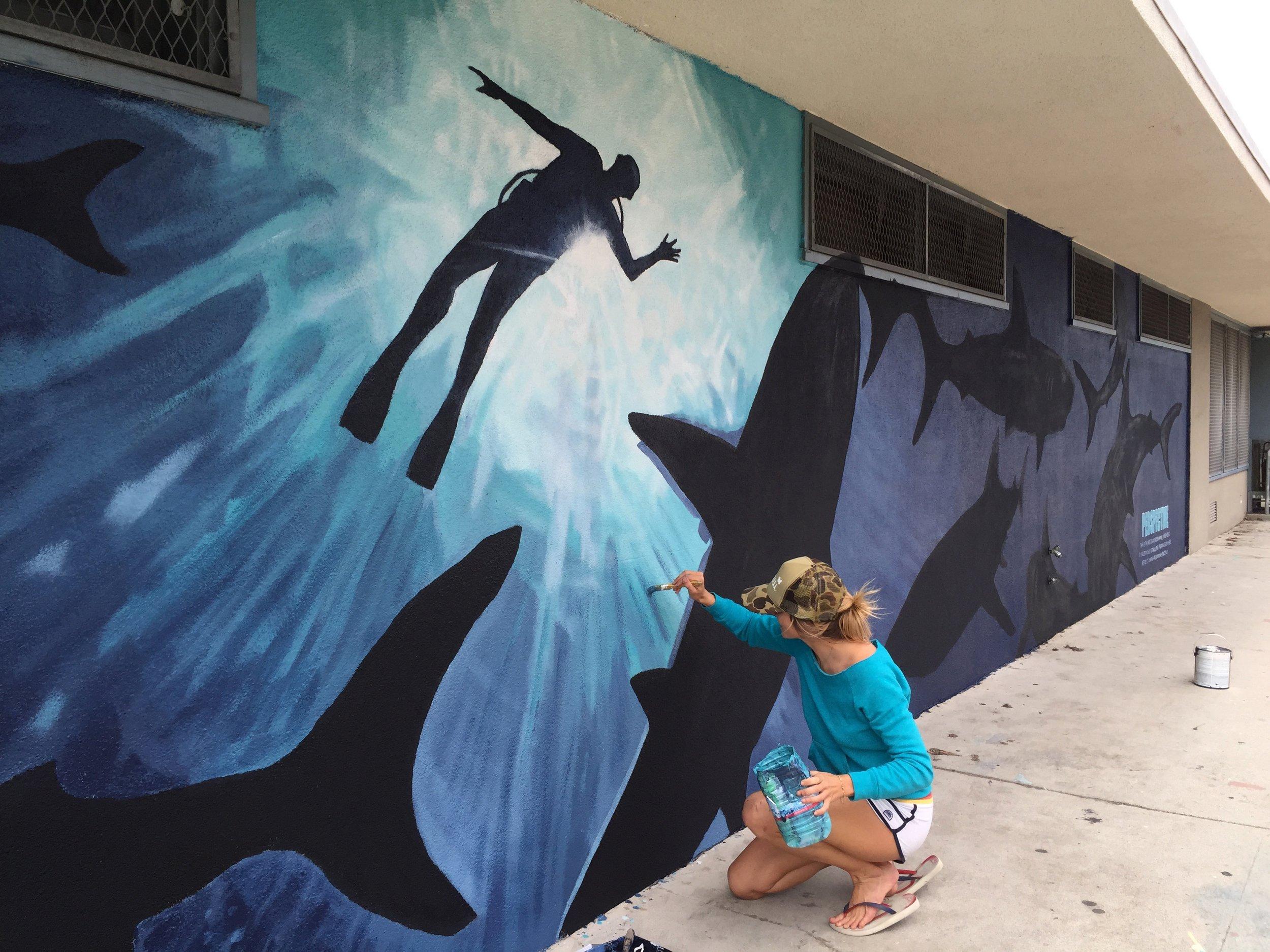 Greta Kruesi putting finishing touches on the shark mural.