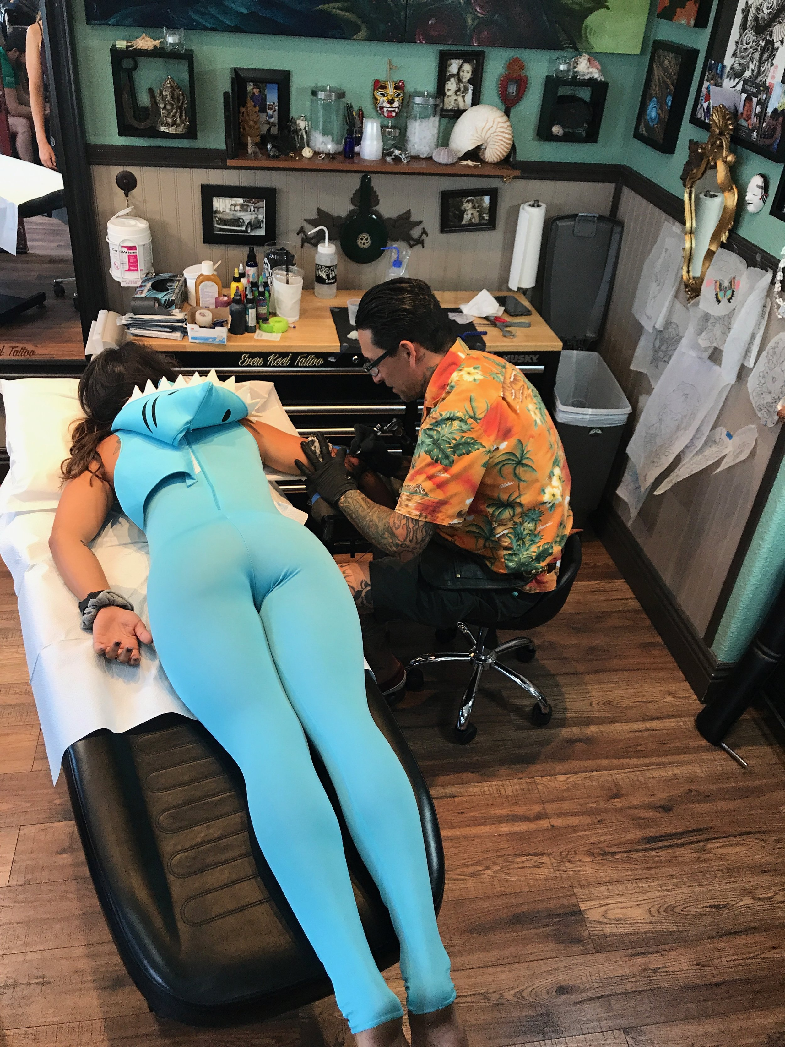 Client in shark costume getting tatttoo