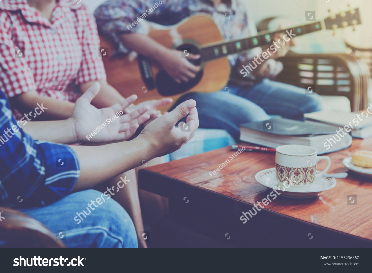 stock-photo-christian-family-worship-god-in-home-with-coffee-cup-donut-and-holy-bible-on-wooden-table-1155296860.jpg