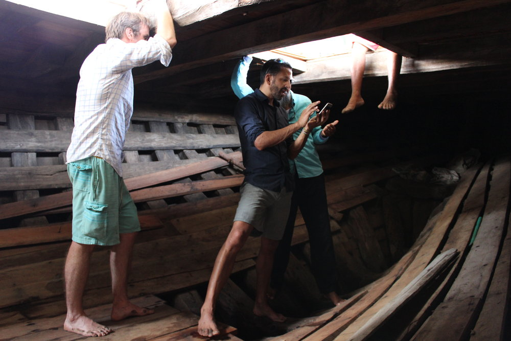 Ben showing visitors inside the hull of a big dhow.