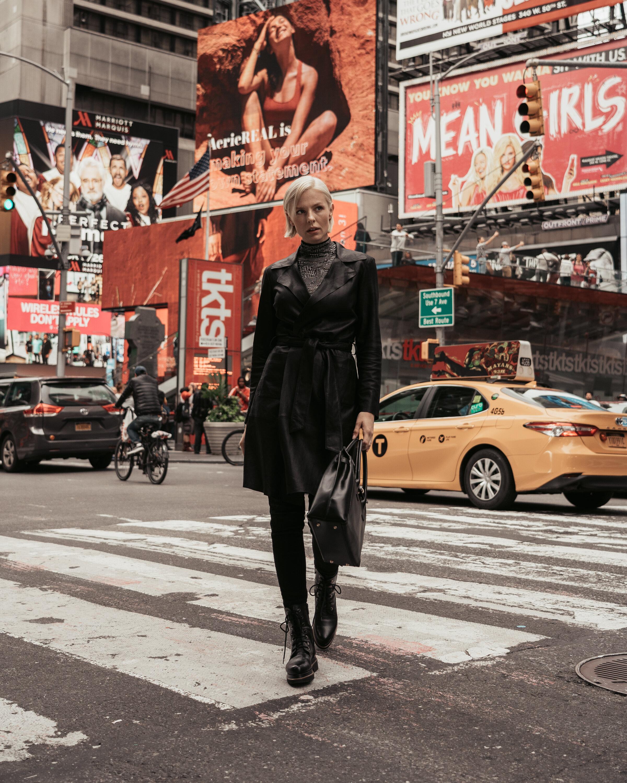 Times Square  Ledermantel aus Ziegennappa Seidenshirt mit Rollkragen Jeans Schnürbotts aus Leder mit dekorativen Ziernieten Tasche