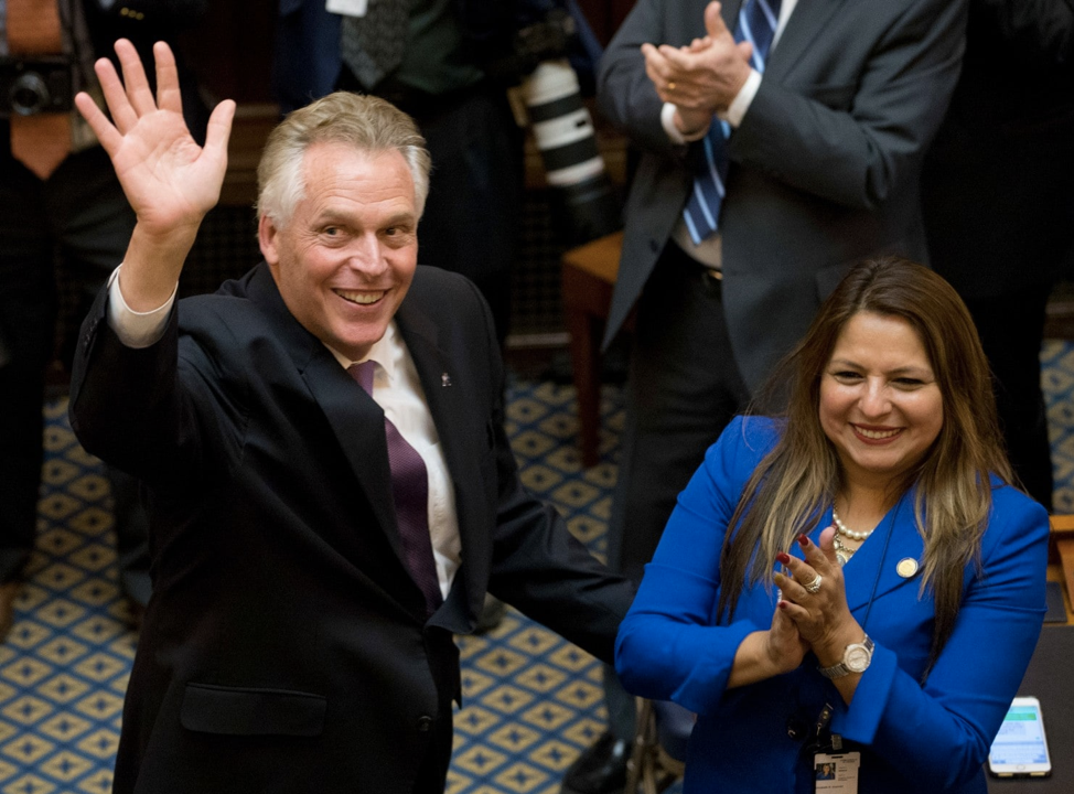 Virginia Gov. Terry McAuliffe waves to the gallery next to Del. Elizabeth Guzman (D-Prince William) as he arrives to address a joint session of the the 2018 General Assembly in Richmond, Va., on Wednesday. (Steve Helber/Associated Press)