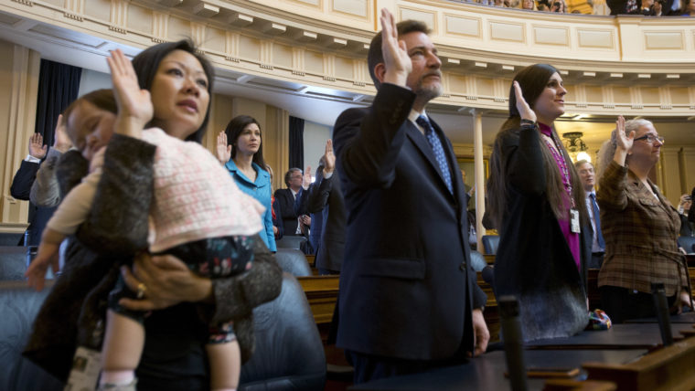 Del. Danica Roem, D-Prince William, second from right, the first transgender delegate, takes her oath of office along with Del. David Reid, D-Loudon, second from left, and Del. Cheryl Turpin, D-Virginia Beach, right, and Del. Kathy Tran, D-Fairfax, left, holding her sleeping daughter Elise, during opening ceremonies of the 2018 session of the Virginia House of Delegates.
