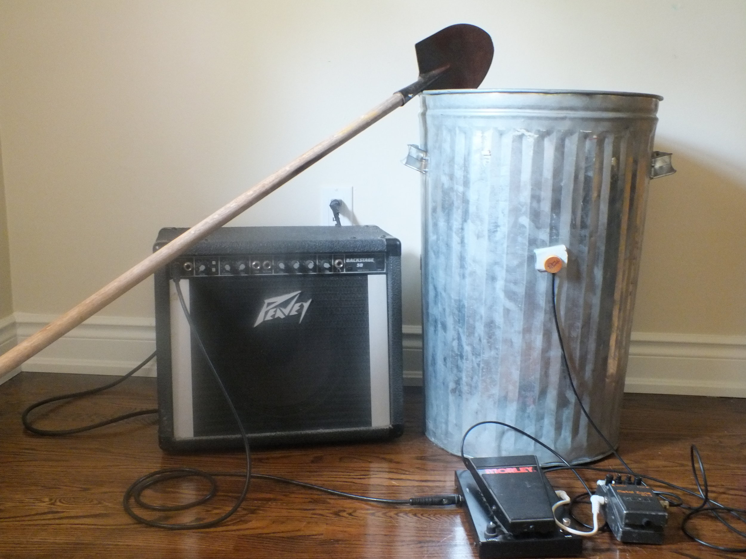 "The  Catherine Wheel,  named after another 18th century torture method which involves tying the victim to a large wheel and crushing their limbs with a sledgehammer (Scott 1959). The REI itself, seen in  figure 7c , is a metal garbage can amplified with a piezo microphone and modulated with a guitar effect unit or a ""stompbox."" The  Wheel  is performed by beating it with a stick or large metal rod, or by stirring/crushing small noise-making materials such as stones, broken-glass, or small pieces of metal. A video of the Catherine Wheel recorded at the Soundasaurus Festival performed by Colin Labadie and myself as the noise-music duo MUGBAIT can be seen here:"