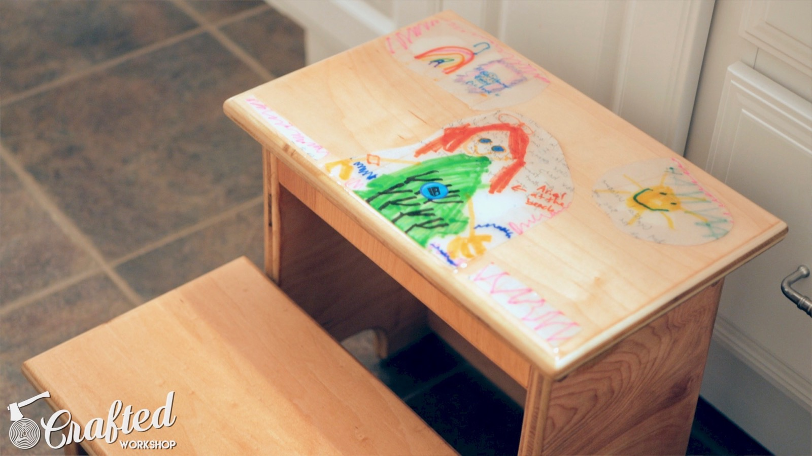 kid's step stool with artwork on top step