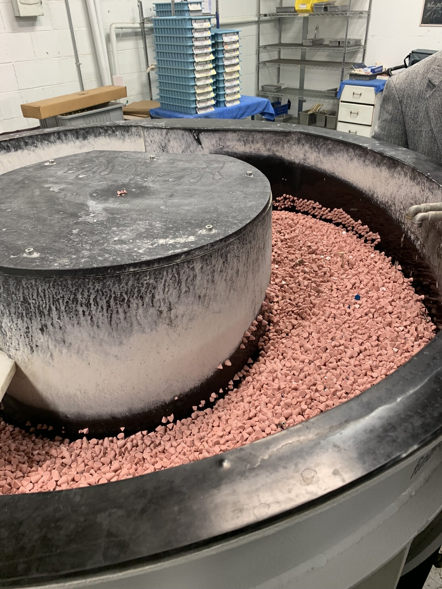 The keys float through these moving polishing rocks to refine the keys prior to assembly.