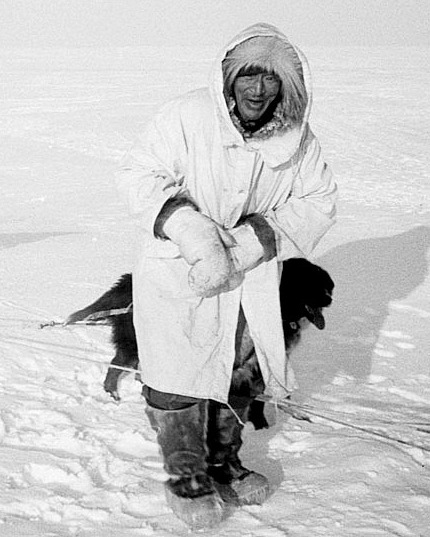 The late Wesley Ekak traveling on the tundra, wearing extremely warm caribou hide parka, boots, and mittens.