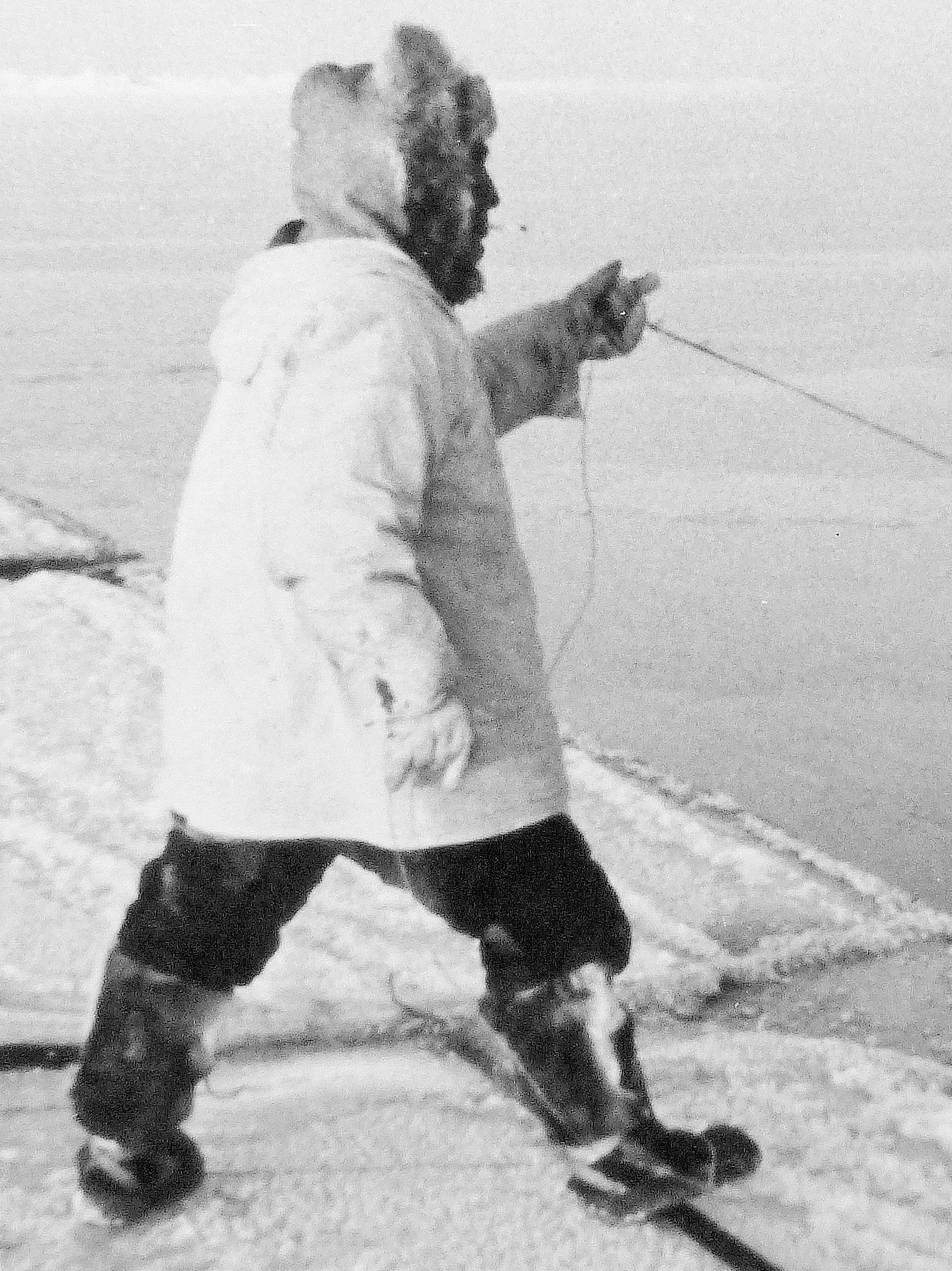 The late Weir Negovanna hunting on the sea ice near Wainwright, dressed in his best caribou hide gear, including boots with waterproof sealskin soles (1965 photos).