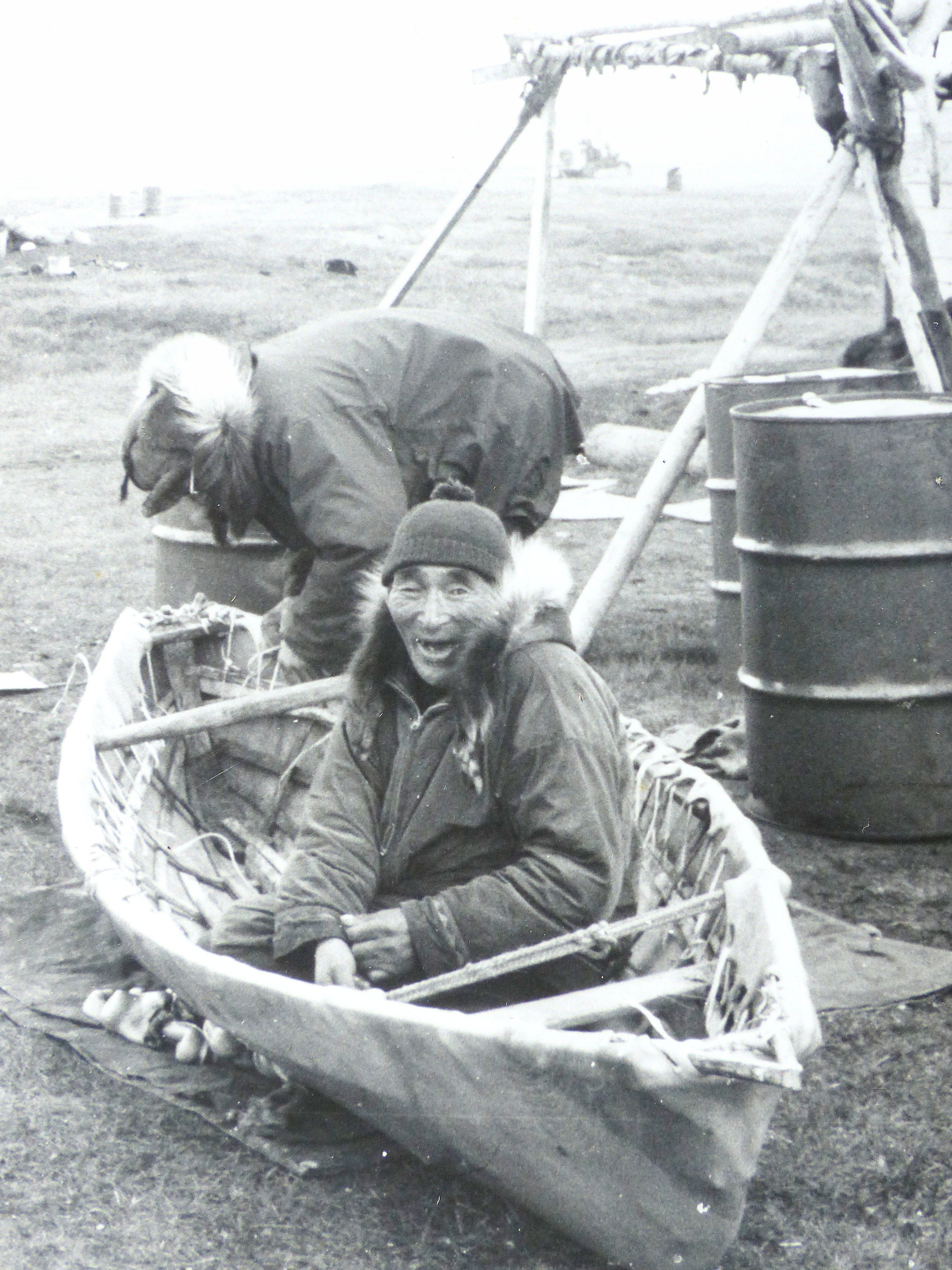 The late Inupiaq elders, Wesley Ekak (foreground) and Waldo Bodfish, lashing the sealskin cover on a small traditional boat (Wainwright village, 1964).