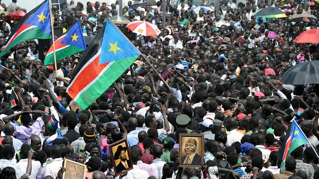 A view of people holding photos of the founding fathers of the Republic of South Sudan, President Salva Kiir (center left) and John Garang (right) during celebrations of the the first anniversary of South Sudan's independance in 2012. Photo by: Staton Winter