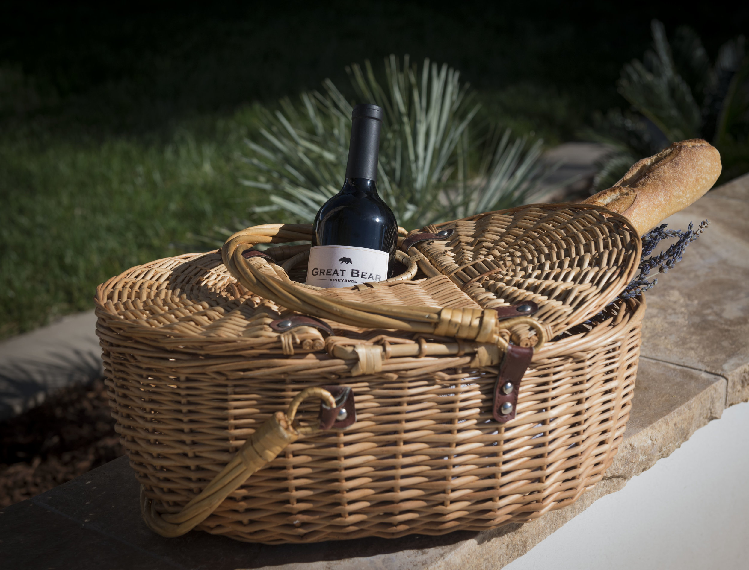 Basket with bottle of Great Bear wine inside and a baguette