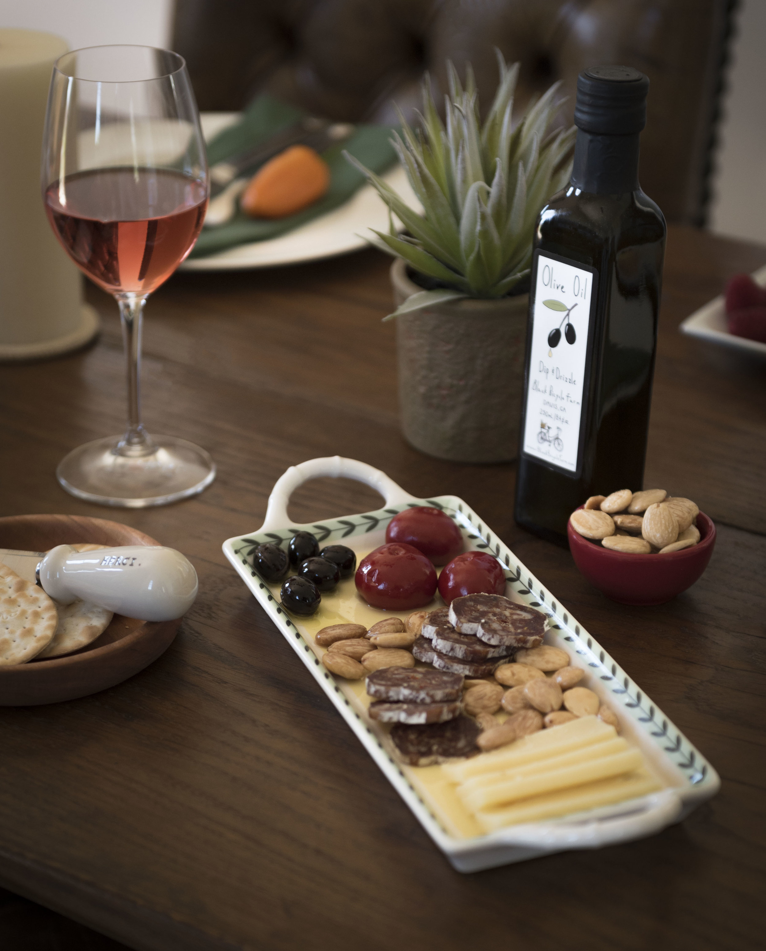 Cheese plate, olive oil, and glass of rosé on a wooden table