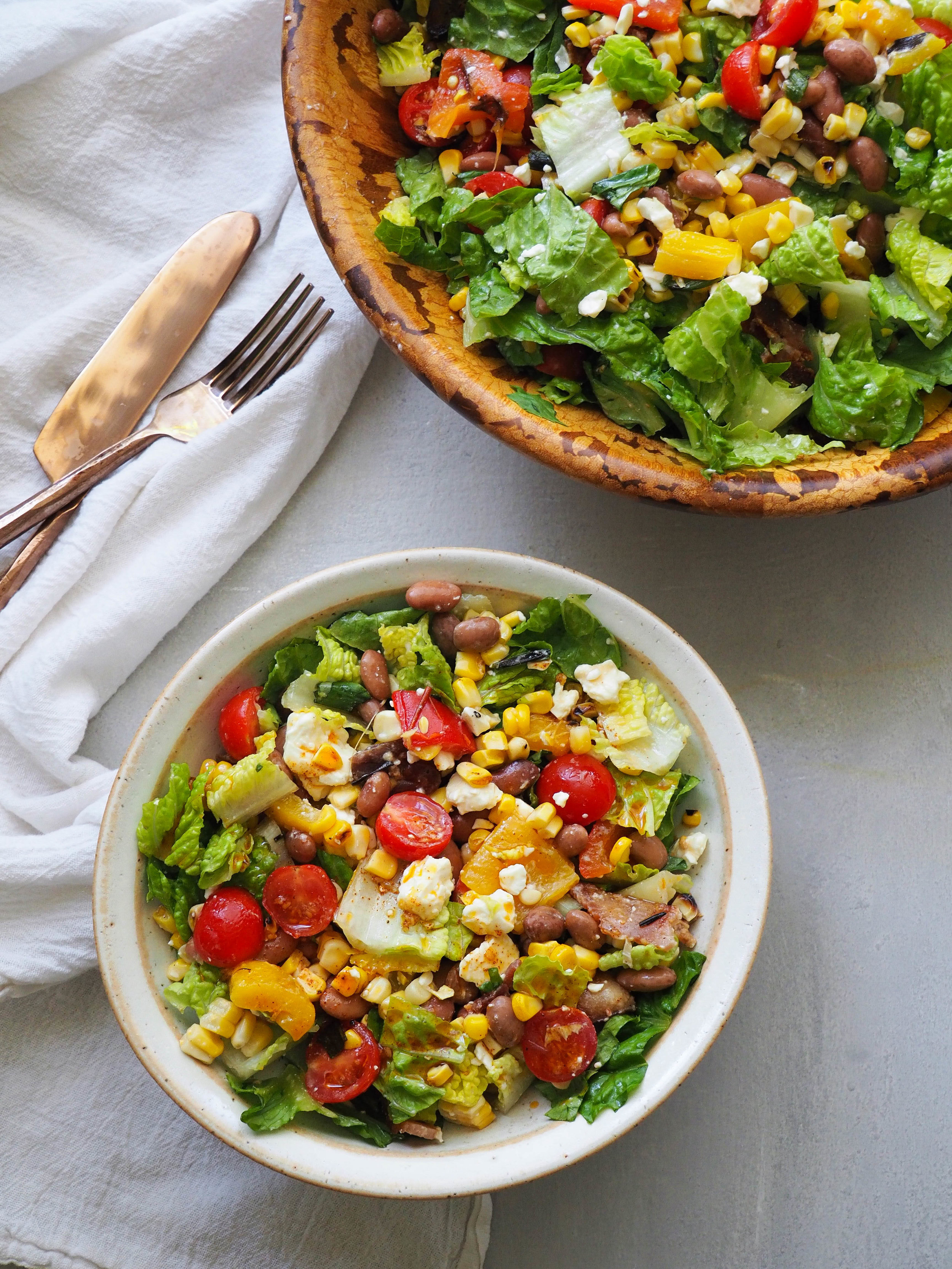 Mexican street corn chopped salad! All the flavors of street corn in this salad of charred corn, grilled peppers, feta, and smoky bacon in a chili lime-vinaigrette! #salad #corn #summer #grilling