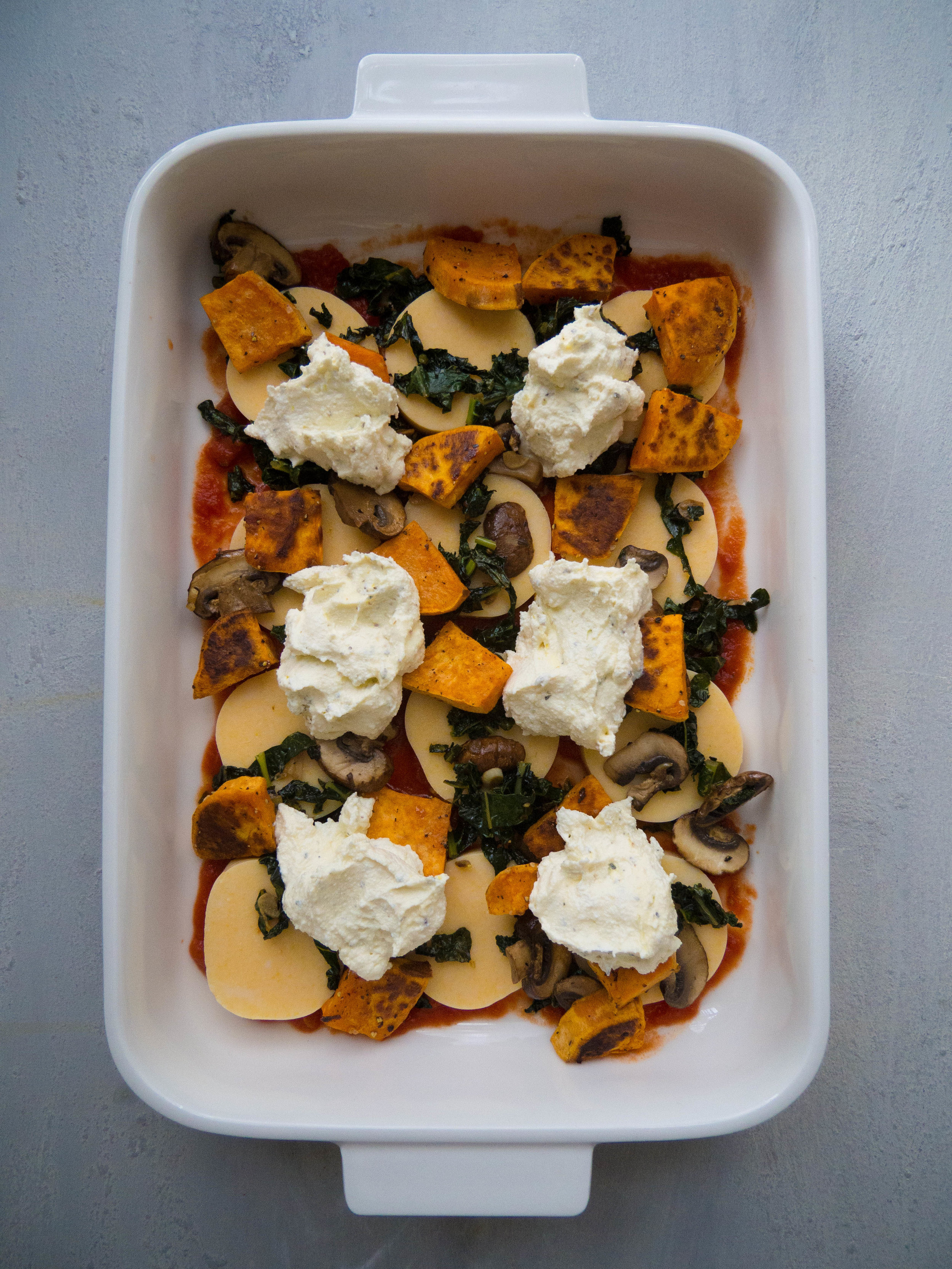 Vegetarian Polenta Lasagna with Kale, Butternut Squash and Mushrooms! It uses slices of precooked polenta tubes in lieu of lasagna noodles, to make it gluten free, and faster to prepare! Packed with roasted, caramelized fall vegetables, spicy tomato sauce and lemony herbed ricotta! #lasagna #glutenfree #fall #winter #pasta #healthyrecipe #vegetarian #kale #mushrooms #wintersquash
