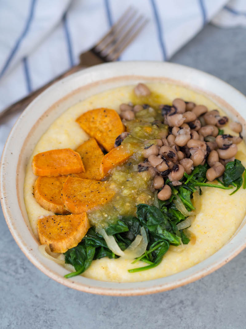Southern goat cheese grits and vegetable bowl! Top creamy stone ground grits with sauteed greens, roasted sweet potatoes, black-eyed peas and salsa verde for a satisfying vegetarian meal! #vegetarian #southernfood #grits #glutenfree #healthy