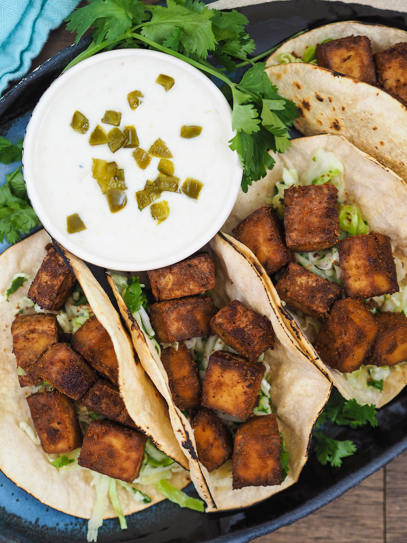 Crispy baked tofu tacos with cilantro lime slaw get a crispy, umami coating from a combination of nutritional yeast and soy sauce! Inspired by the best vegetarian tacos I've had on a trip to Sonoma! #vegan #vegetarian #taco #tofu #healthyrecipe