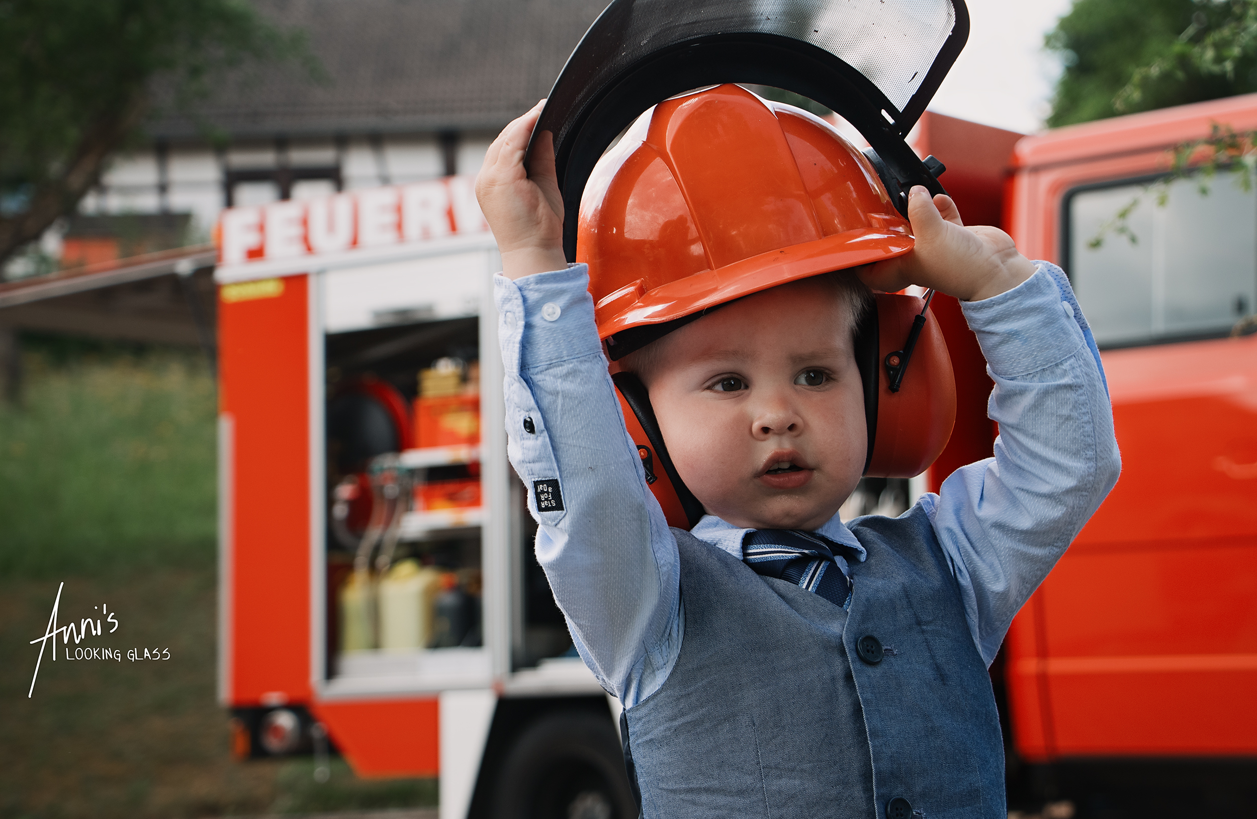 A toddler playing with a firefighter's helmet