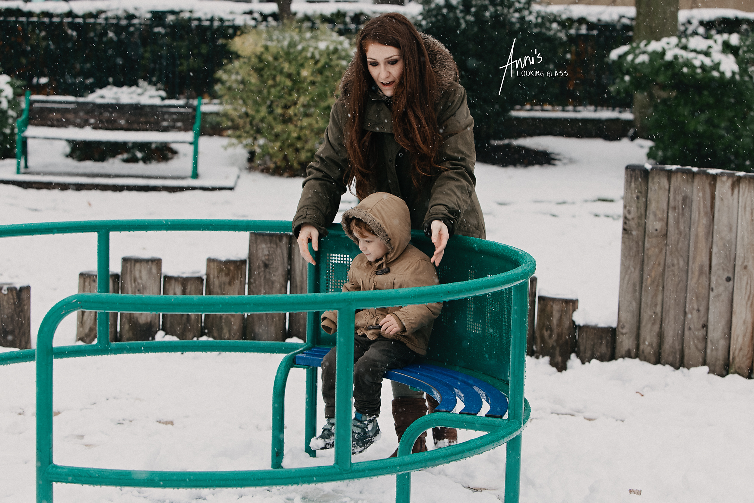 A mother spins her young son on a roundabout in the middle of a snowy playground