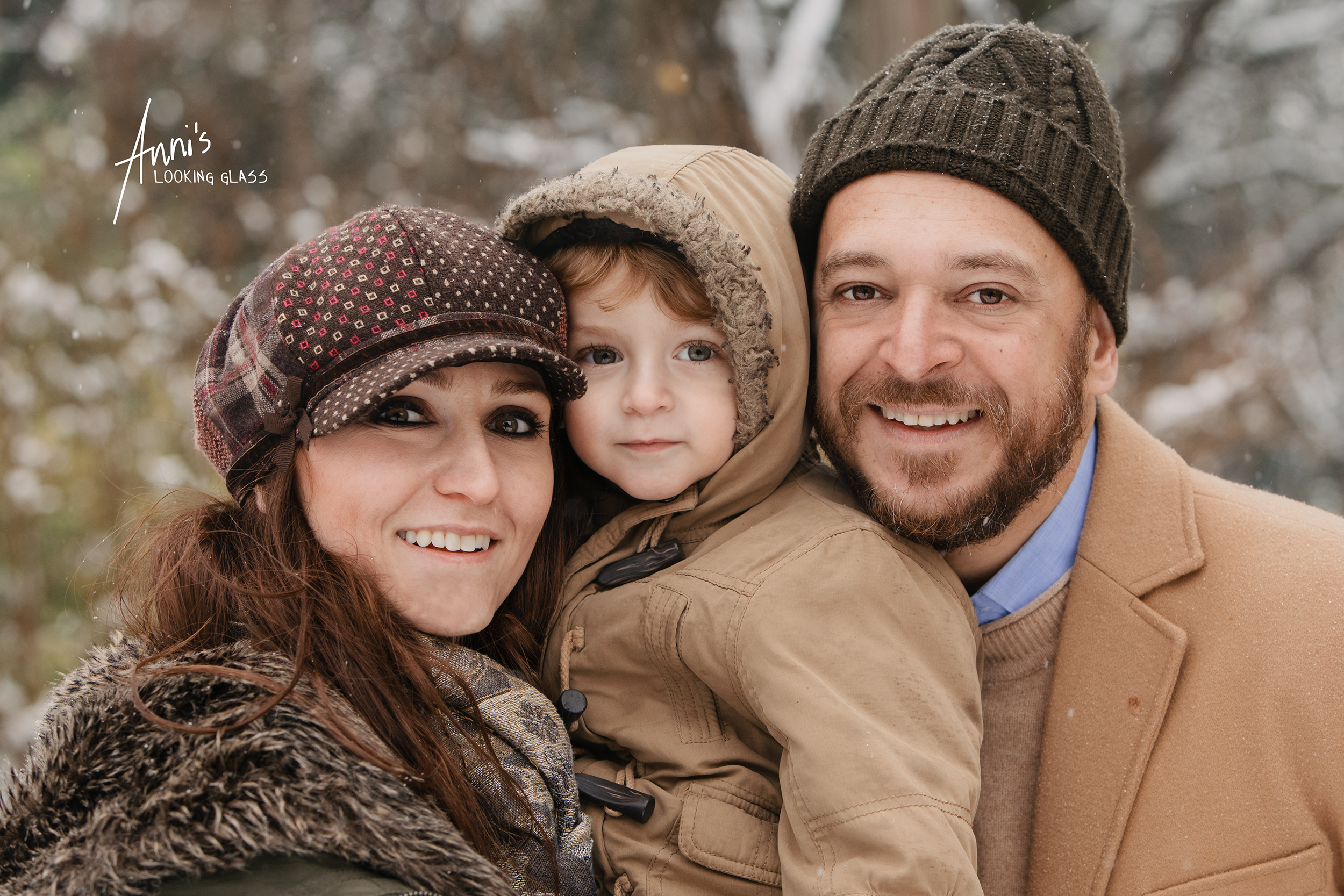 A father and a mother holding her young son smile at the camera wearing winter clothes