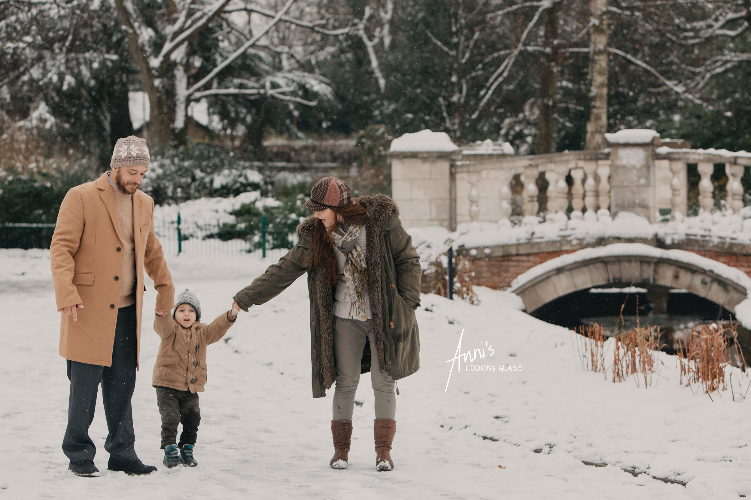 A father and mother walk with their toddler son between in a winter scene at Queens Park, Loughborough