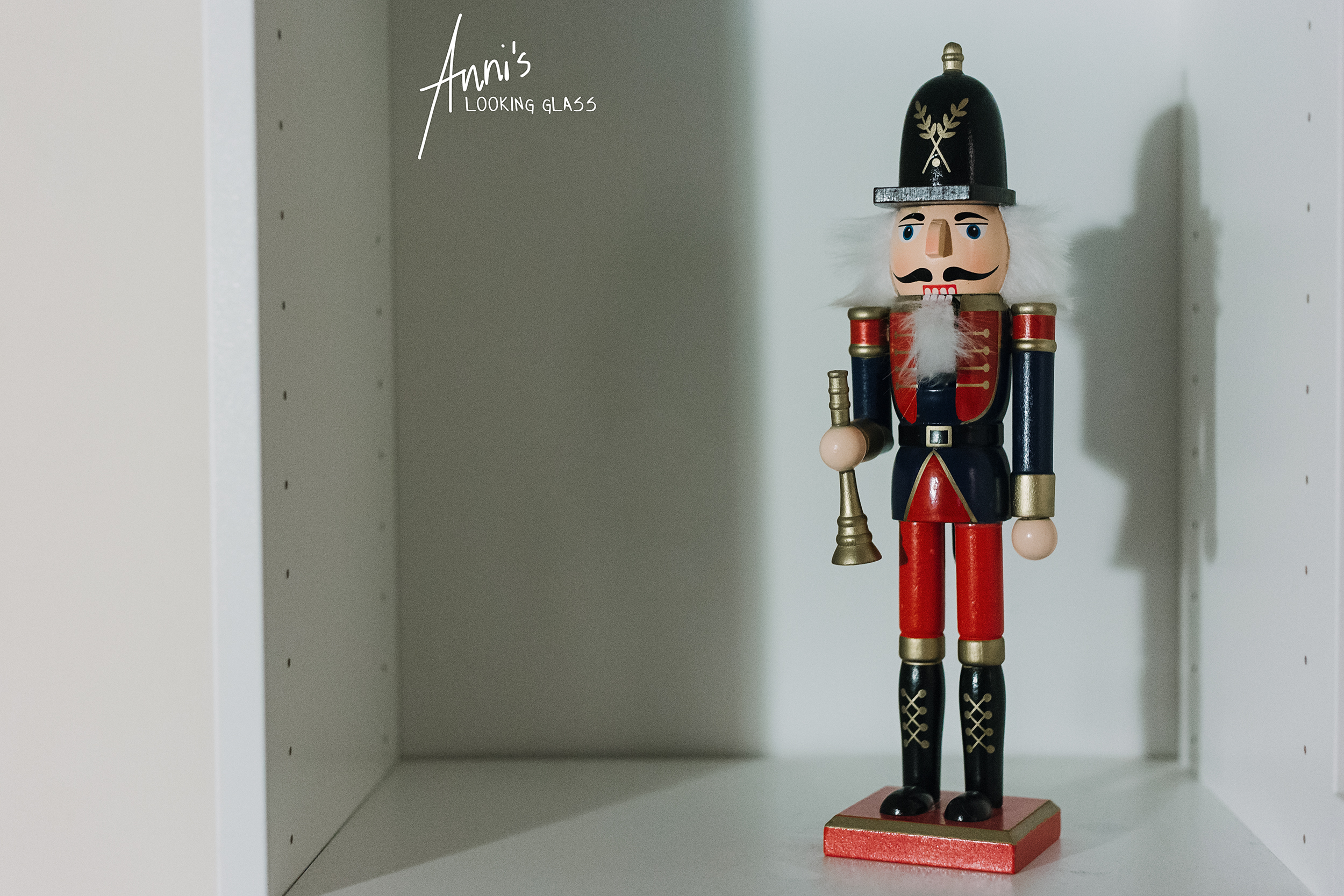 A red and blue nutcracker sitting in a white shelf