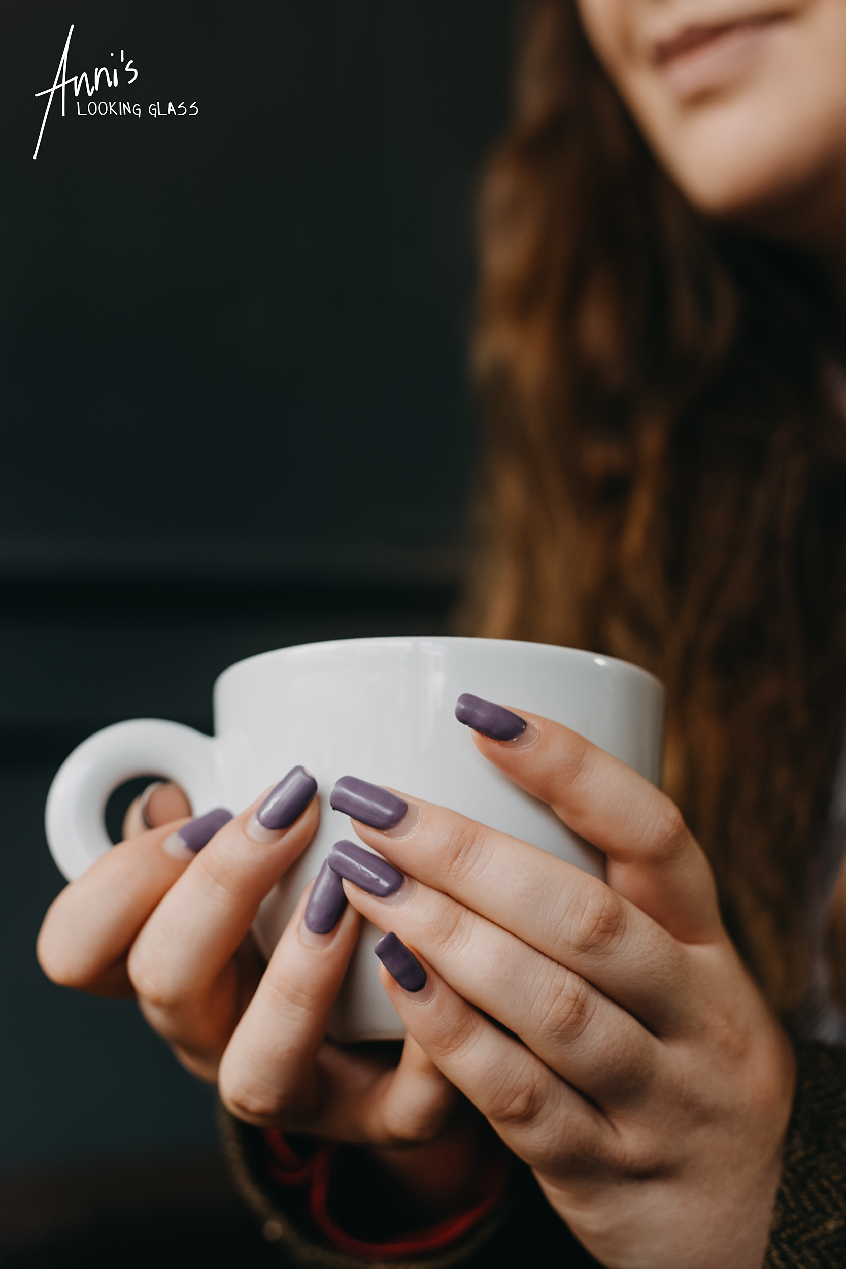 A young girl's hand with nails painted in lilac hold a coffee mug at a Loughborough bar and restaurant