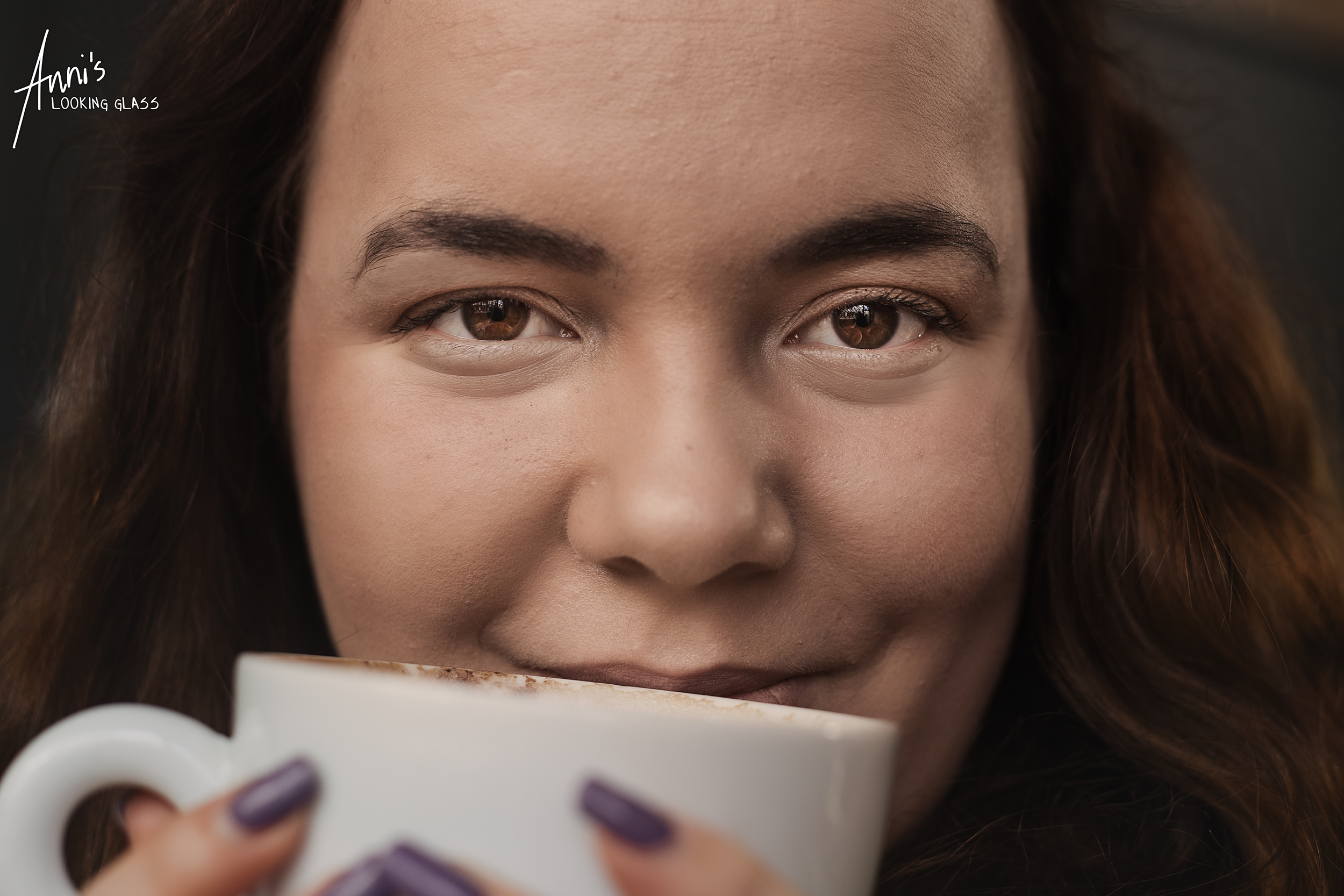 A close up of a young girl holding a mug close to her face inside a Leicestershire coffee shop