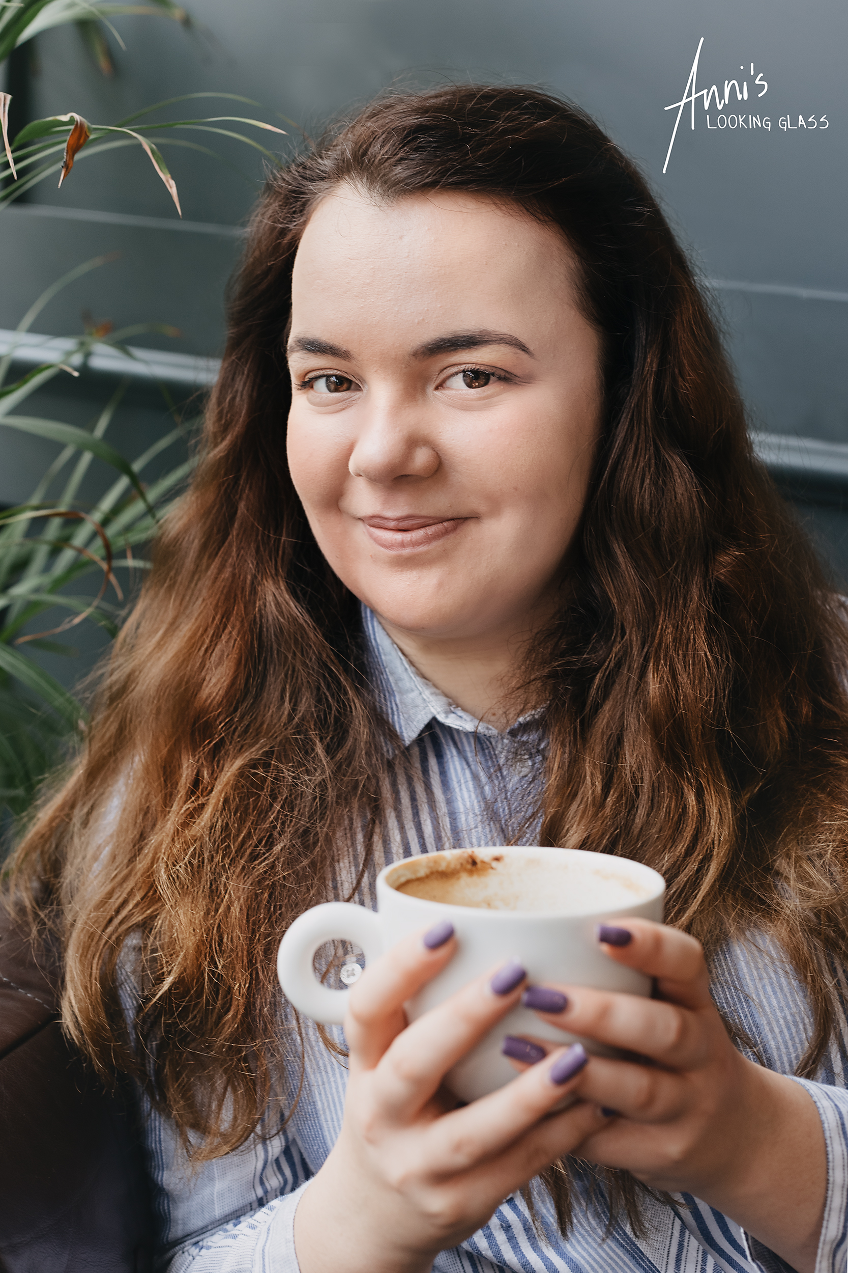 A young woman holding a cappuccino sitting inside a Loughborough coffee shop
