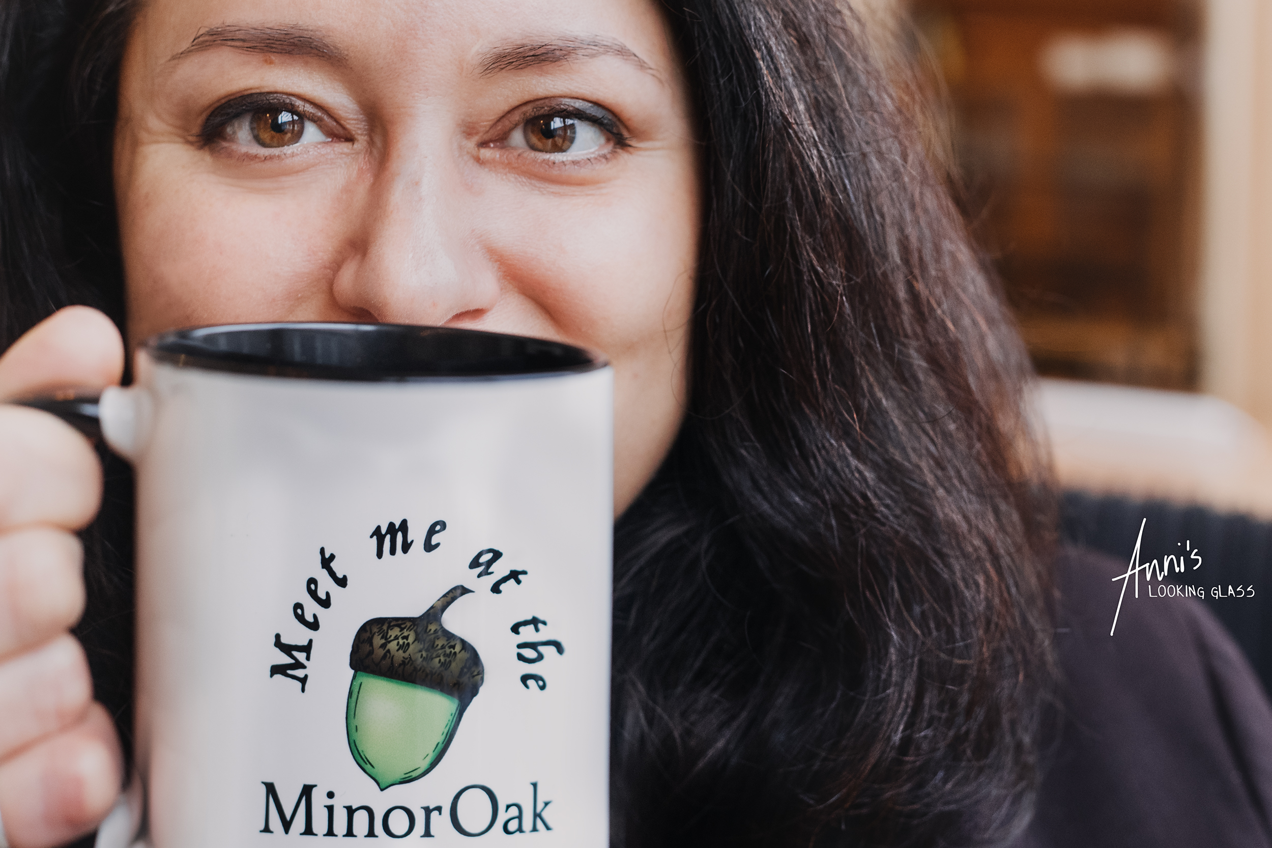 Woman with dark hair holding a branded mug from MinorOak Nottingham Coworking