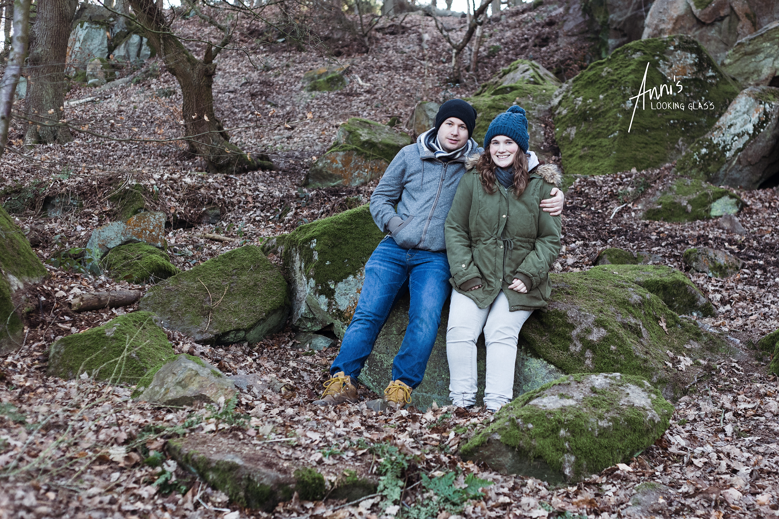 A man and a woman sitting on a rock in the Outwoods near Loughborough, Leicestershire