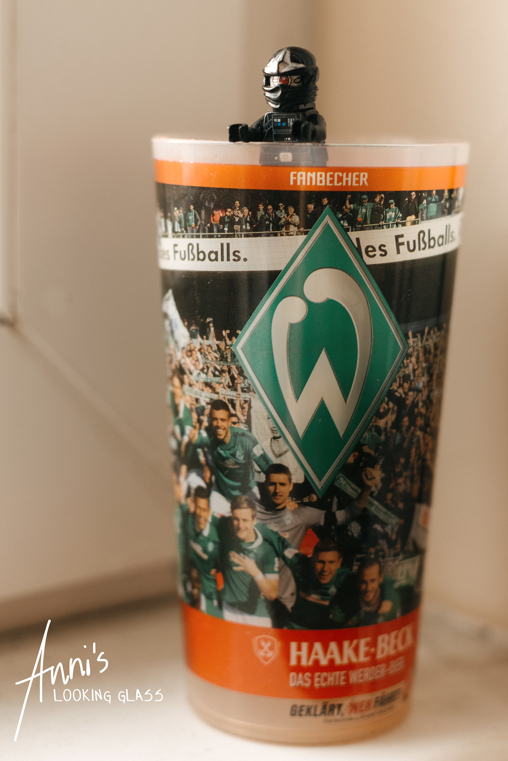 A Lego figure sitting in a Werder Bremen branded plastic cup