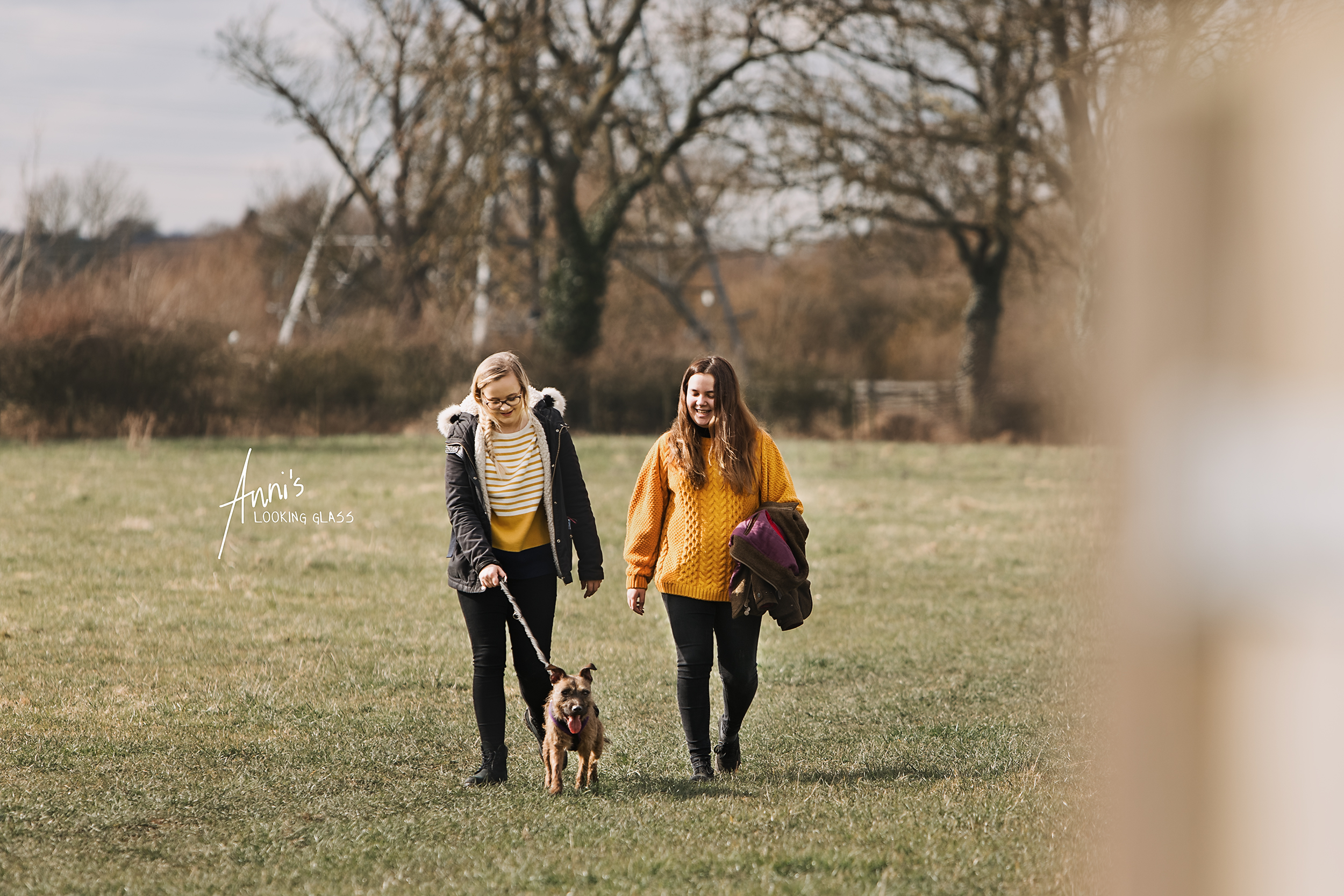 Dog photographer in Loughborough | Two young women walking a border terrier cross in a field near Hathern, Leicestershire | 6th March 2018.