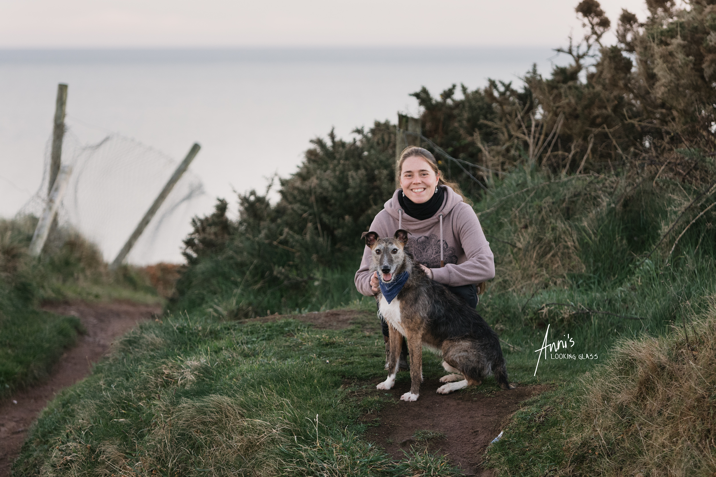 Dog Photographer Loughborough, Leicestershire: A greyhound wearing a blue bandana and a young woman in front of a coastal view in Co. Waterford, Ireland. 24th April 2018