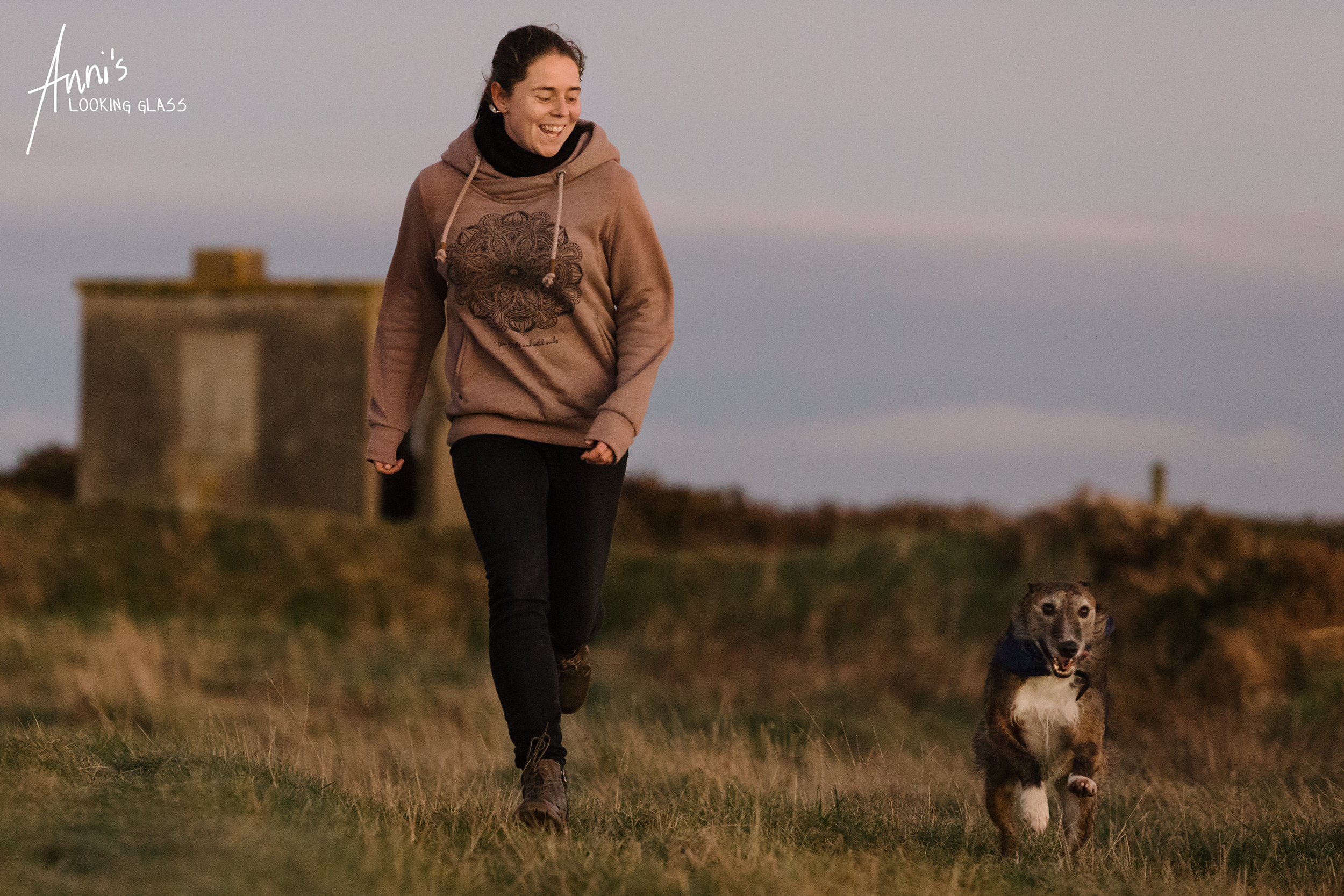 Dog Photographer Loughborough, Leicestershire: A greyhound wearing a blue bandana and a young woman racing acrosse a field in Co. Waterford, Ireland. 24th April 2018