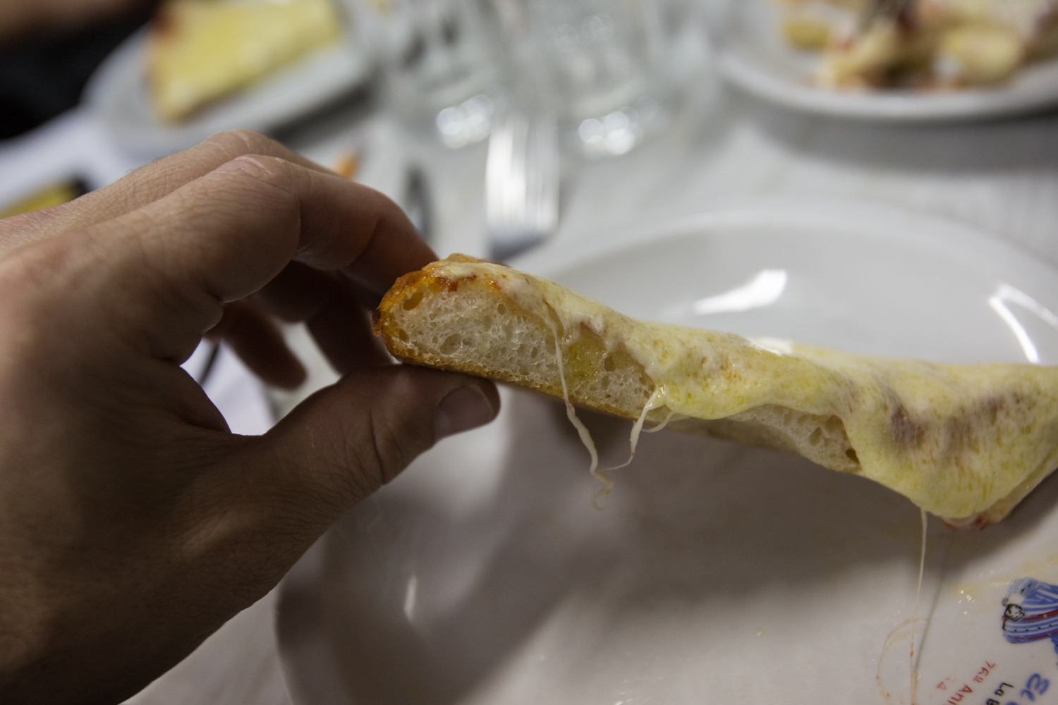Side view of El Cuartito's soft and crunchy crust.