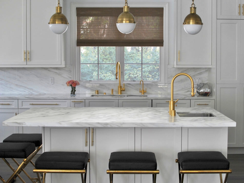 A Saghian-designed kitchen featuring satin brass finishes as well as his leather  bar stools .